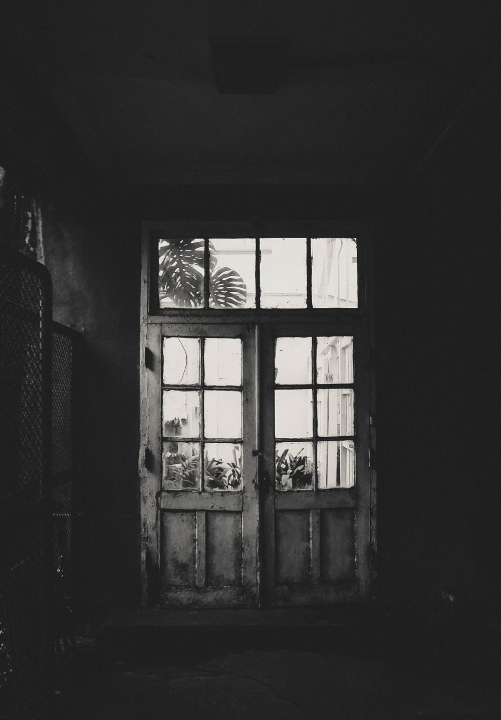 grayscale photo of wooden framed clear glass door