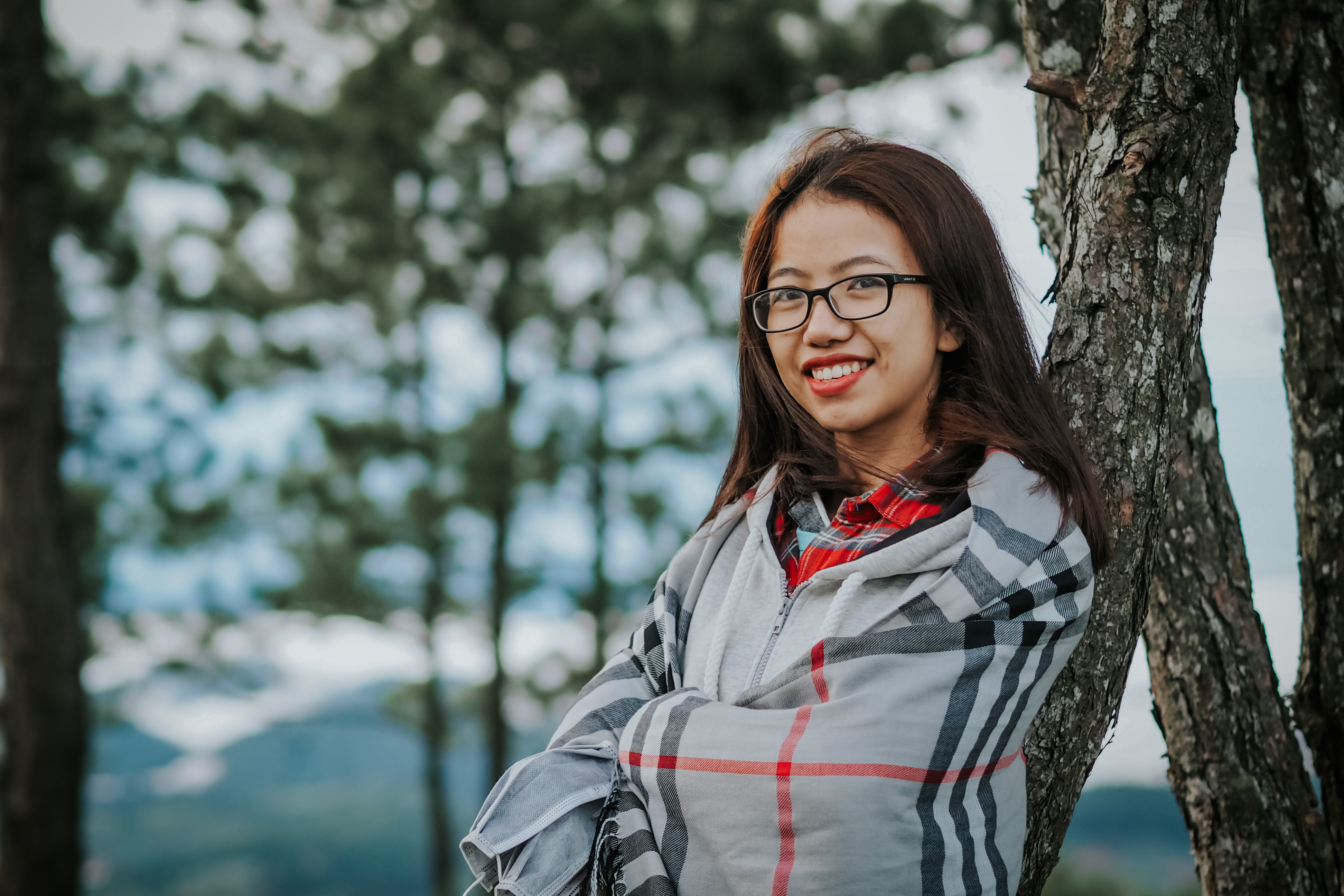 A smiling woman in glasses and a plaid cape leans against a tree in Dalat