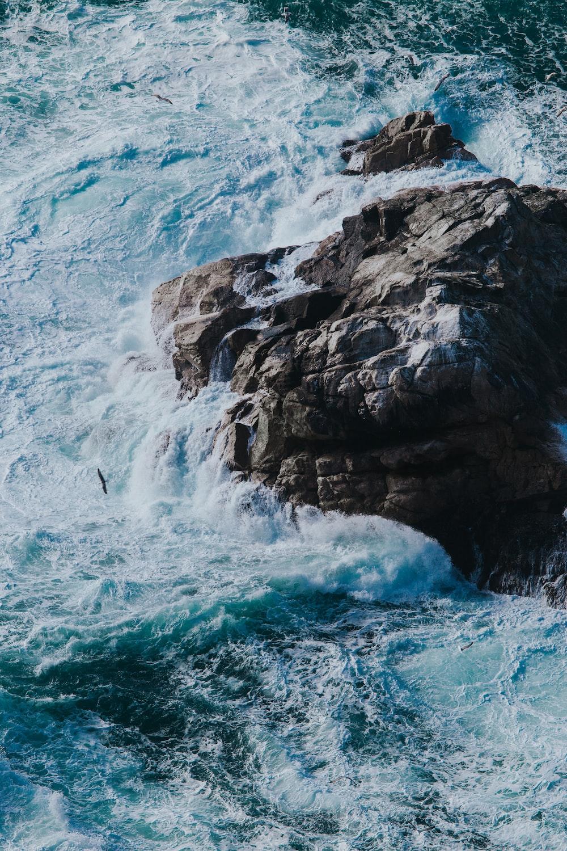 aerial photograph of sea wave splashing on rock