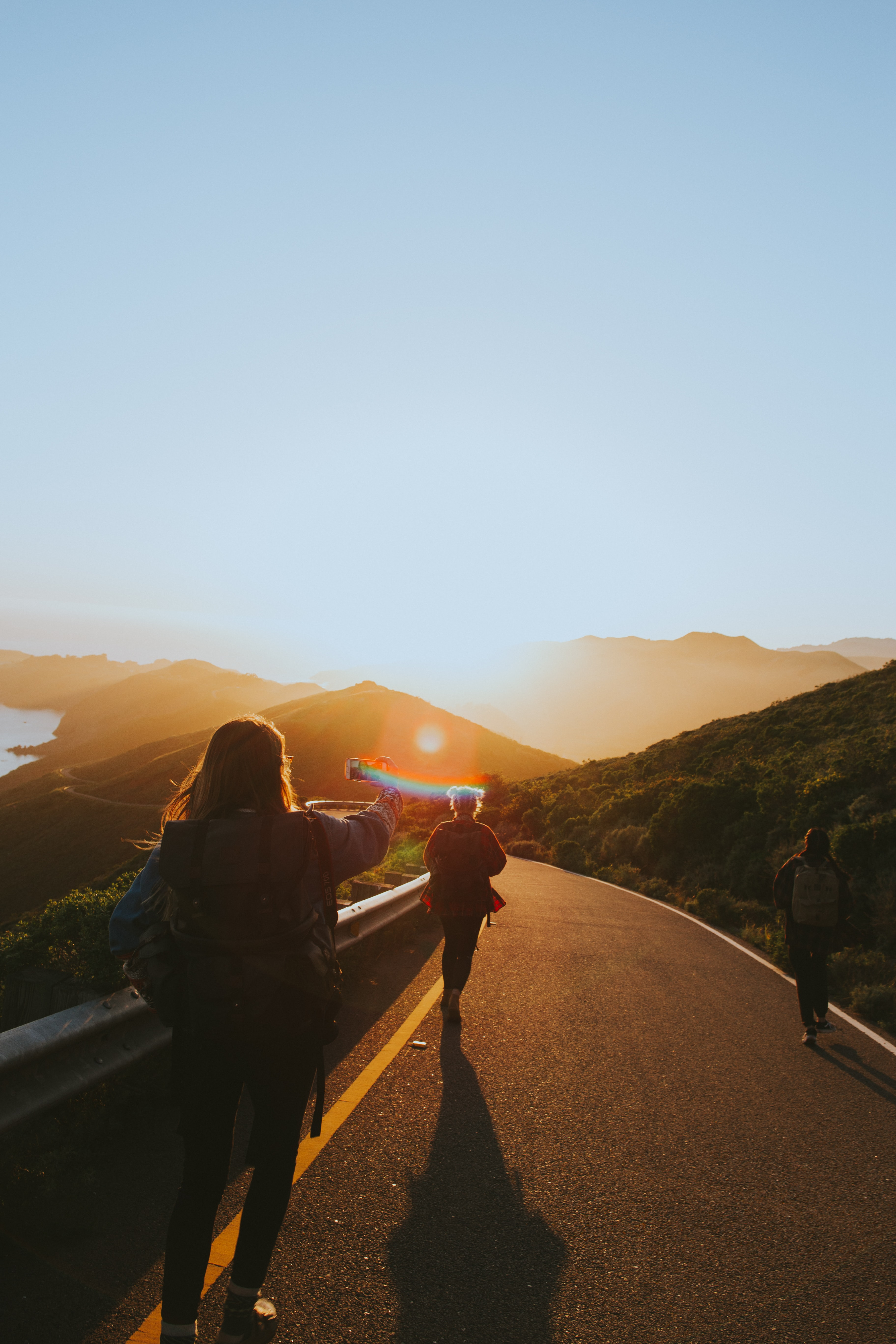 People walking down a hill while one of them takes a selfie on their cellphone during sunset