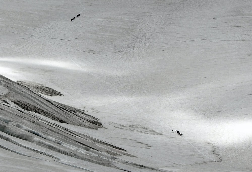 aerial photography of people walking on mountain field with snow