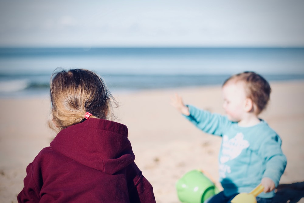 two toddler's sitting on seashore