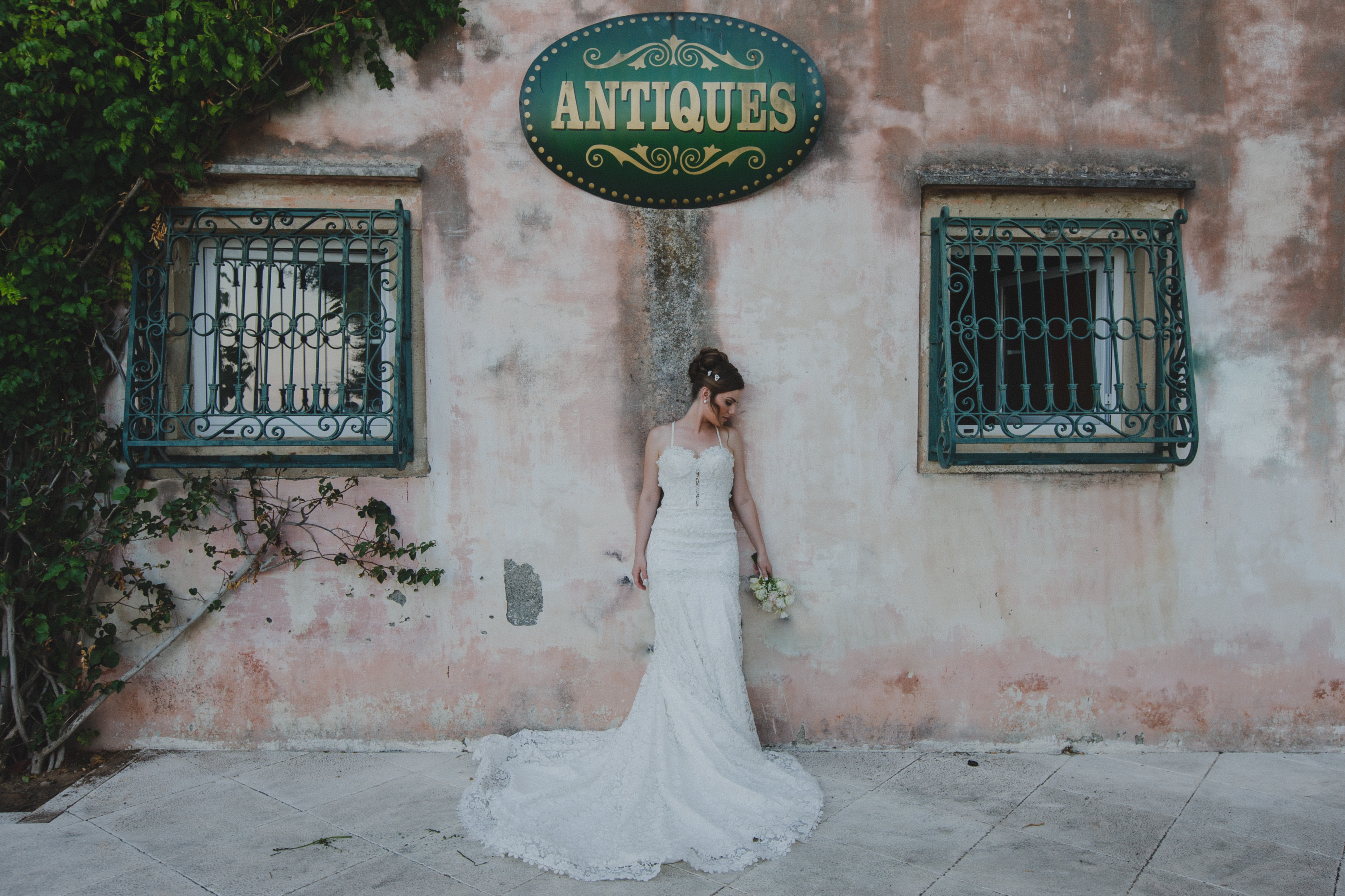 """A woman with styled hair in a white wedding dress carrying a bouquet of flowers beside a fading pink wall with gated windows, growing ivy, and a sign that says """"ANTIQUES"""""""