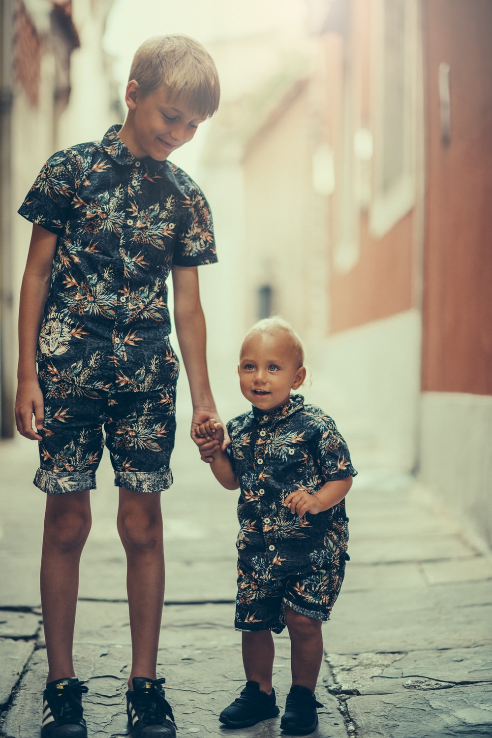 matching pair of boy's black and gray floral collared shirt and shorts standing on gray concrete area