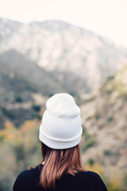 woman wearing knit hat facing through mountains