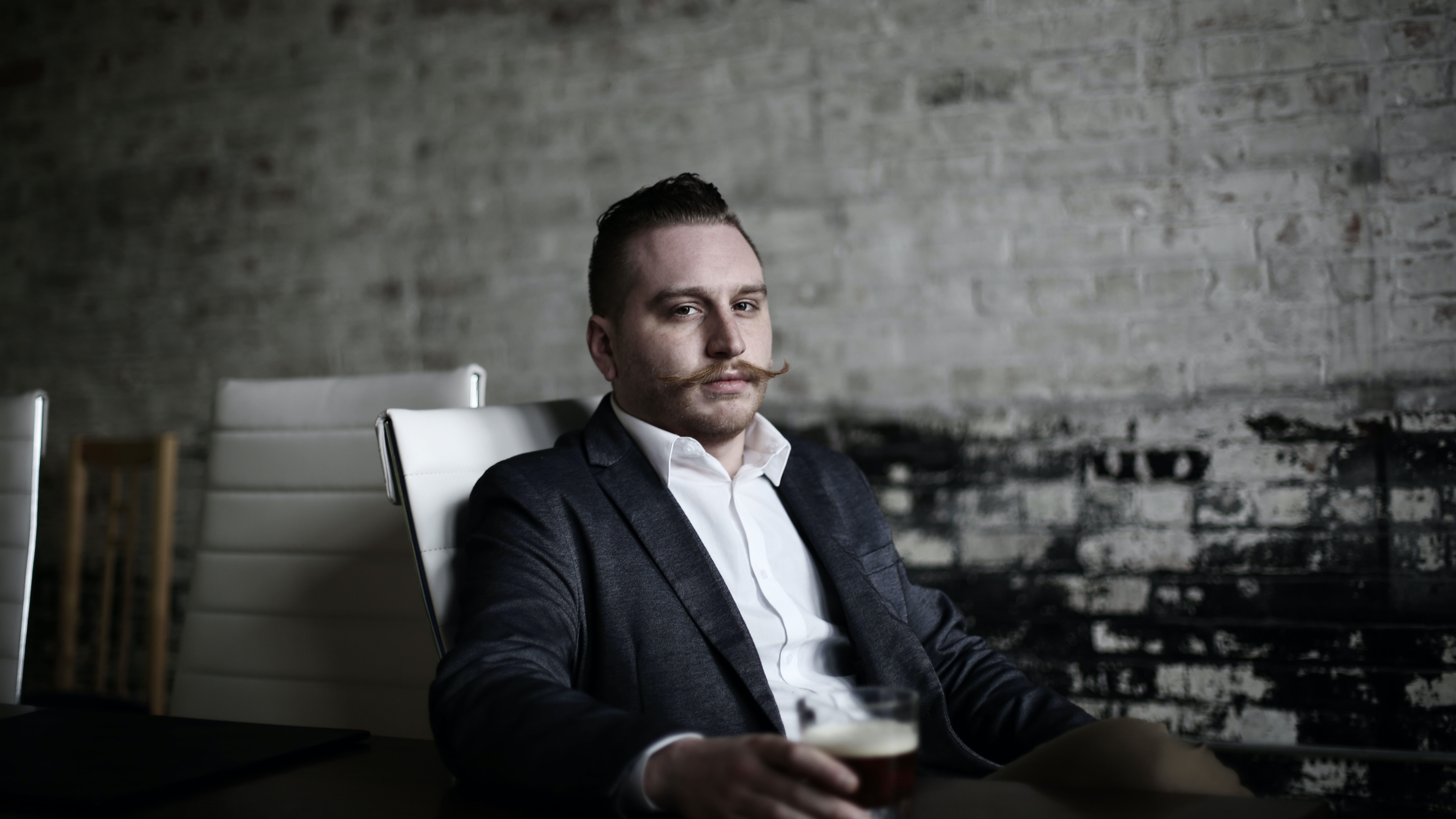 Hipster businessman with a mustace sitting in an office chair