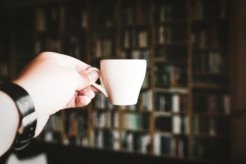 person holding teacup at daytime