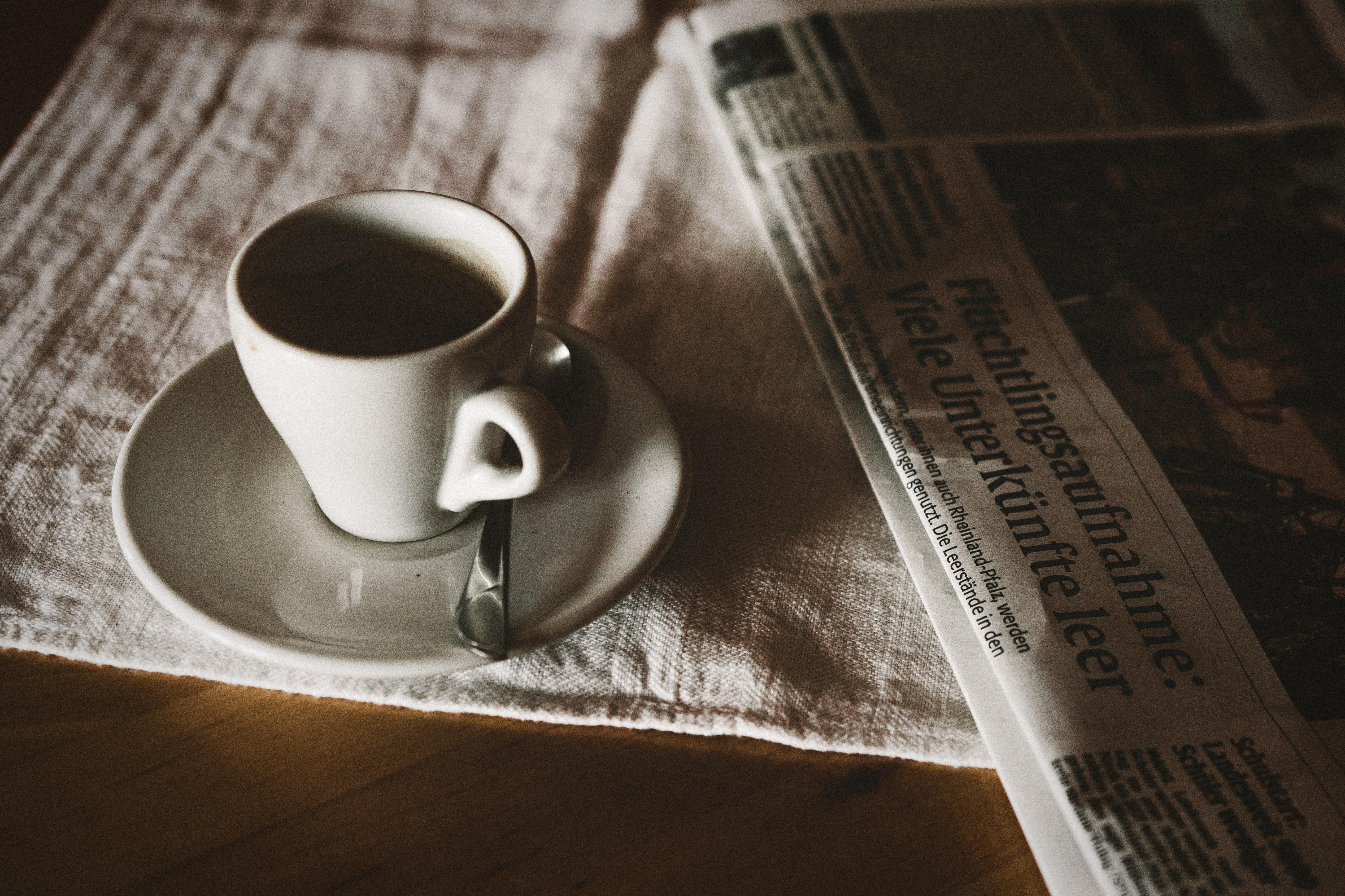 teacup on saucer near newspaper