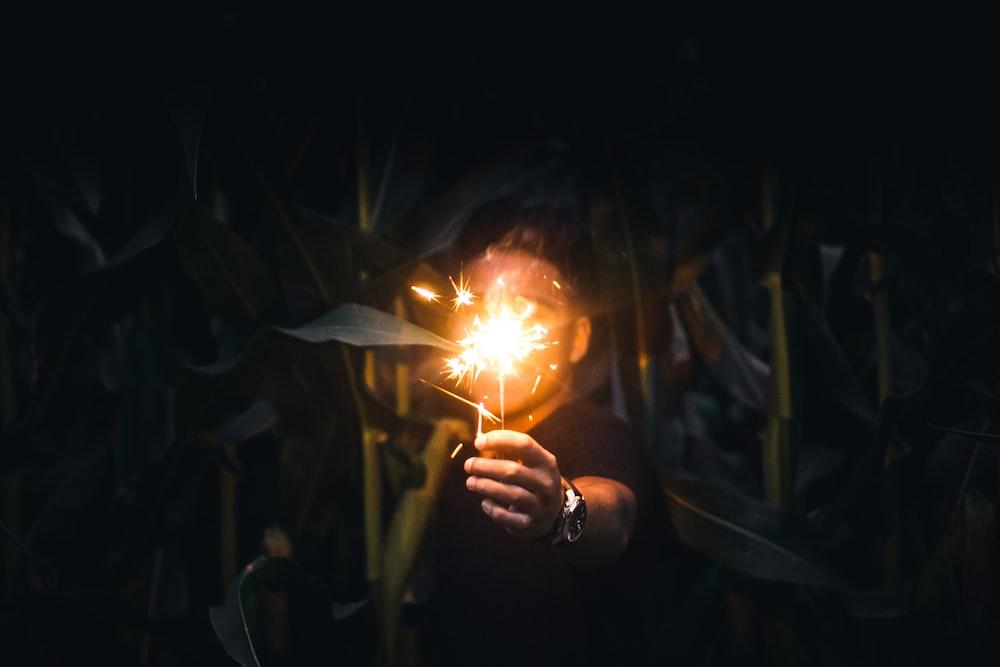 man holding sparkler at nighttime