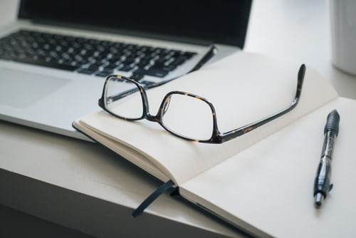 A pair of glasses and a pen on an open notebook next to a laptop