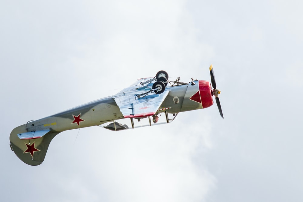 gray and red airplane making a stunt