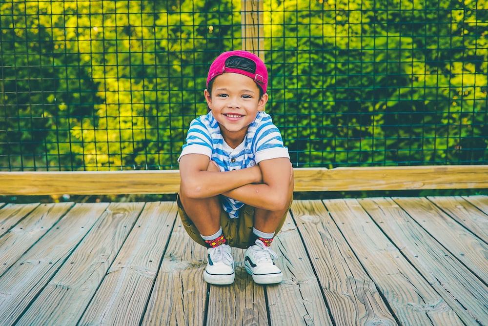 boy on wooden porch near railing