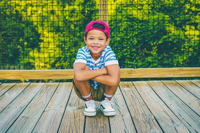 boy on wooden porch near railing kid teams background