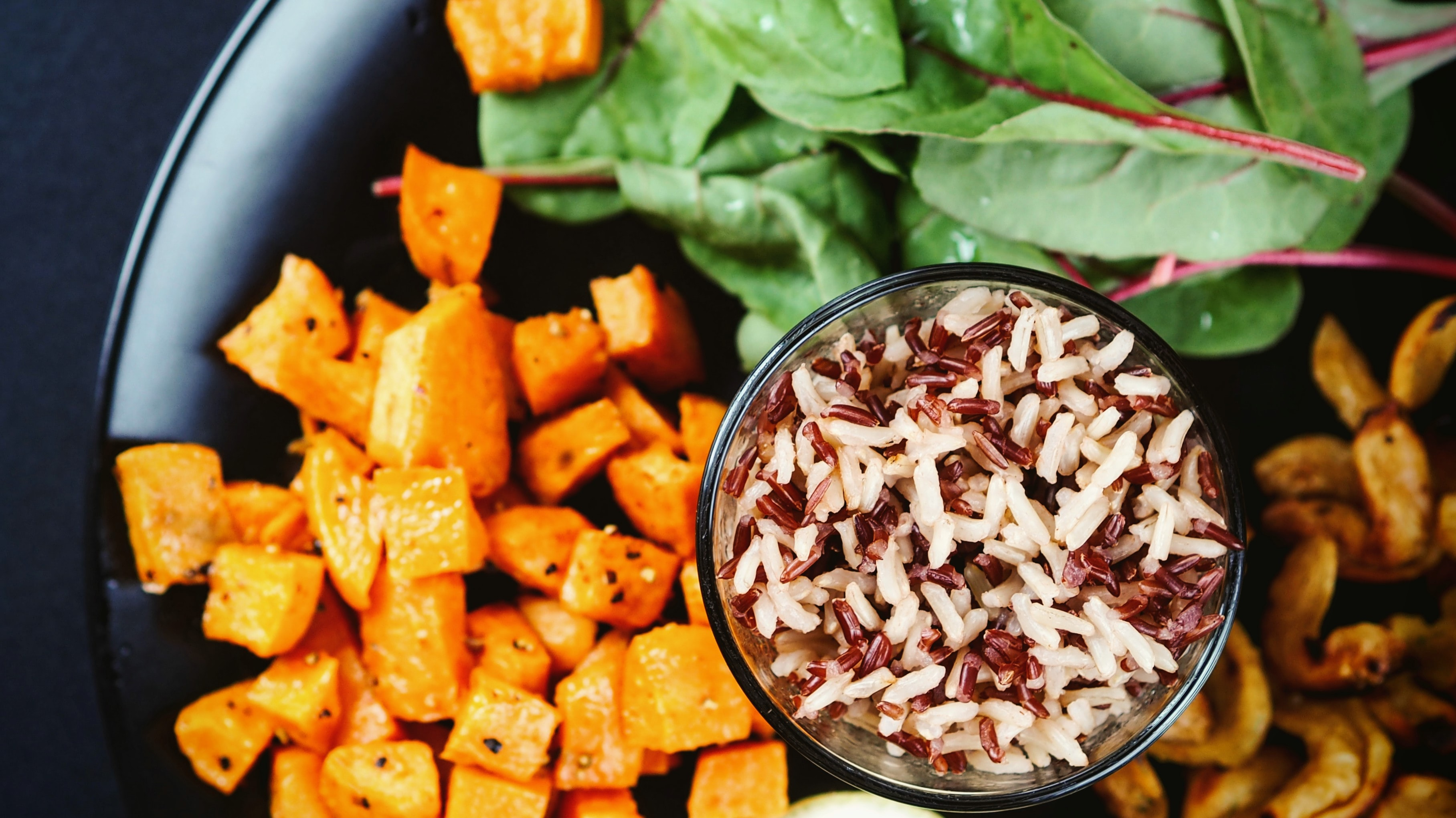 A glass of mixed red and white rice on a plate of salad greens, cooked shrimp and diced sweet potatoes