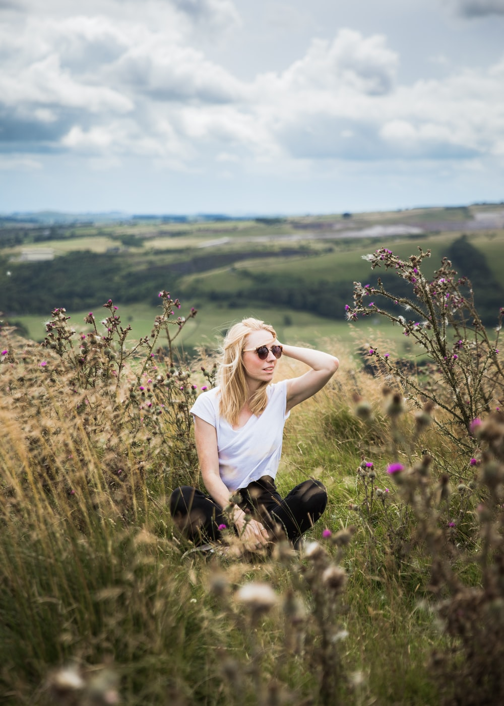 selective focus of woman sitting on green grass in an open field at daytime
