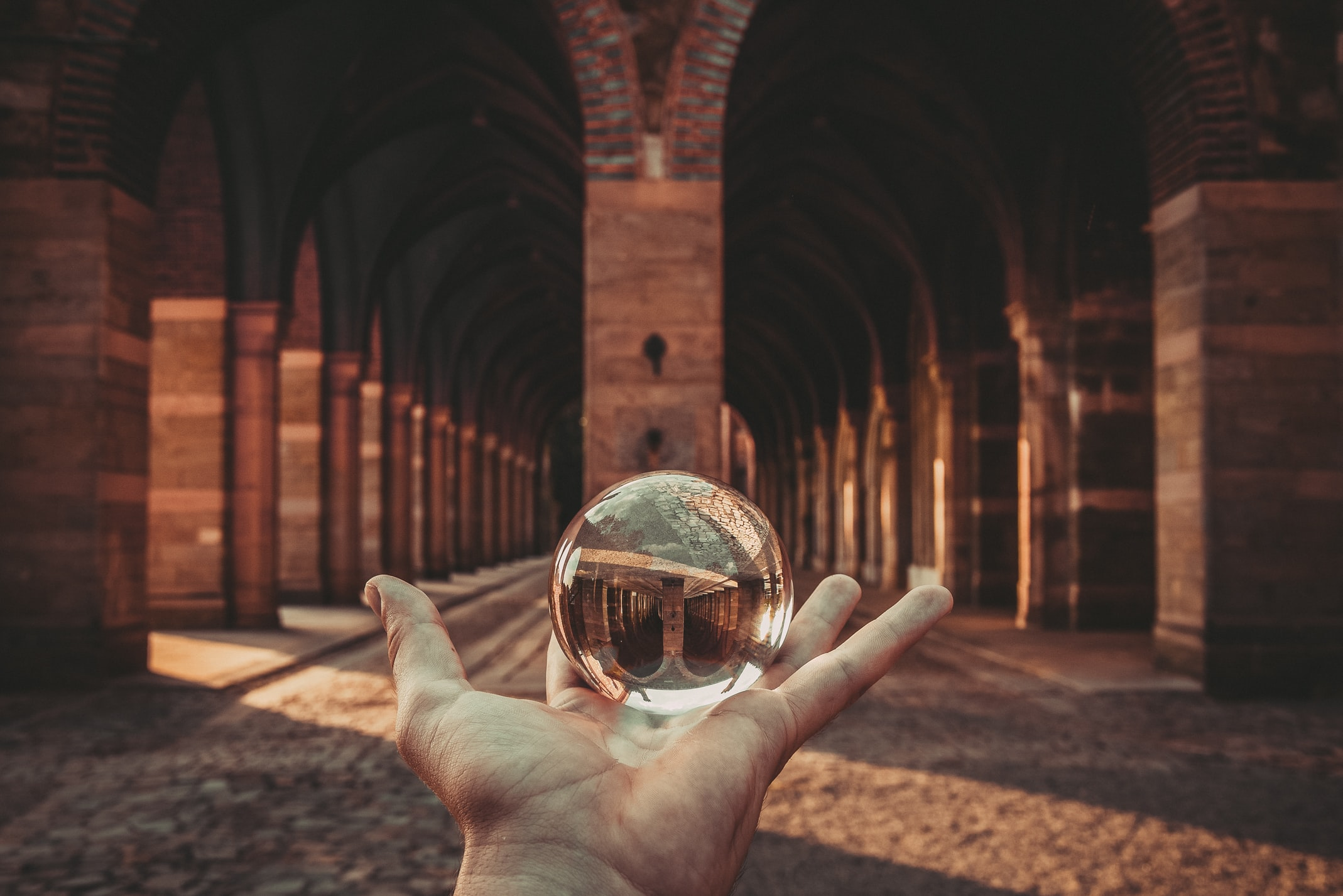 Hand holding a reflective glass orb near an arched hallway
