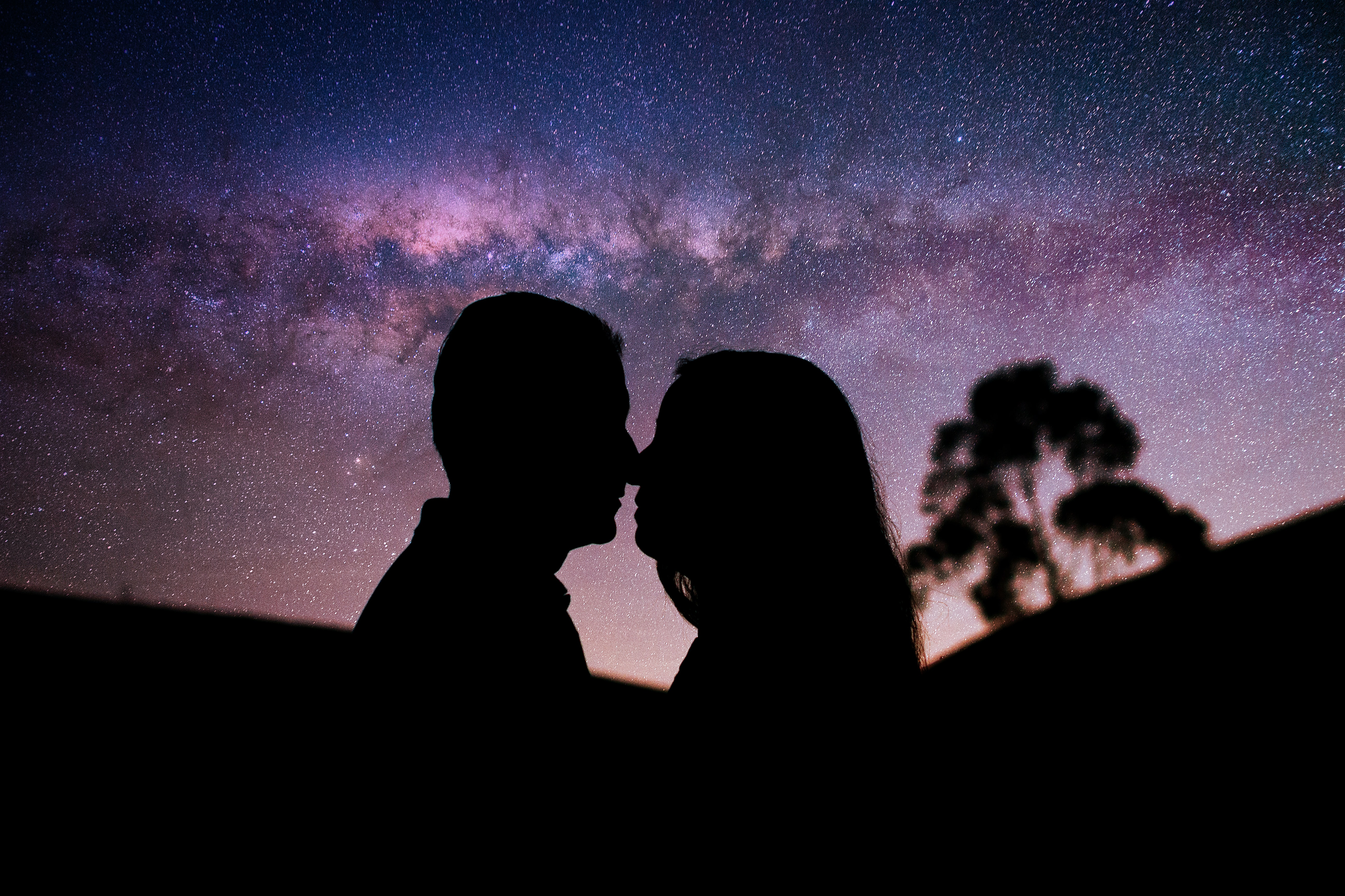 silhouette of man and woman facing each other with milky way background