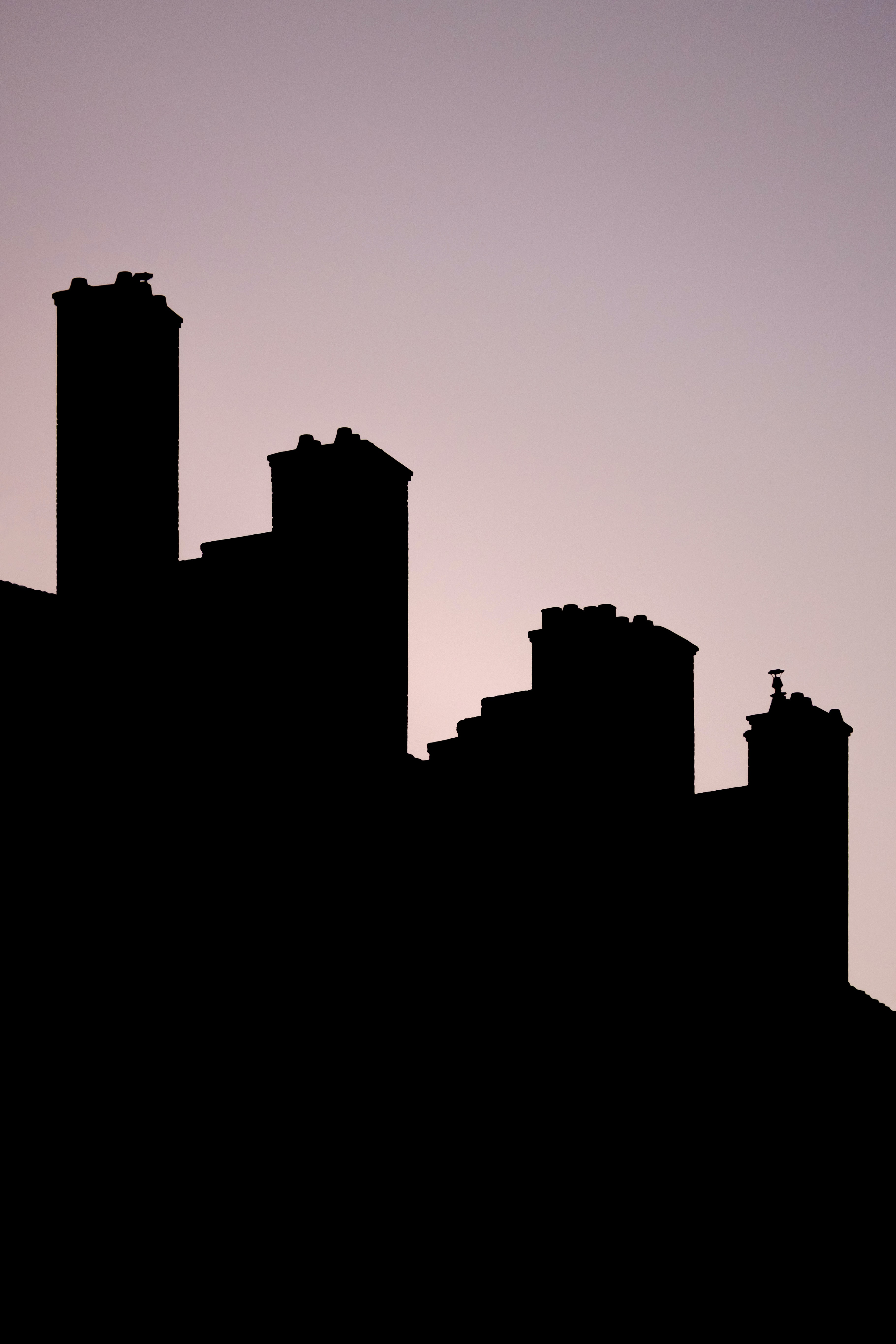Silhouettes of buildings in Lyon under a pale evening sky