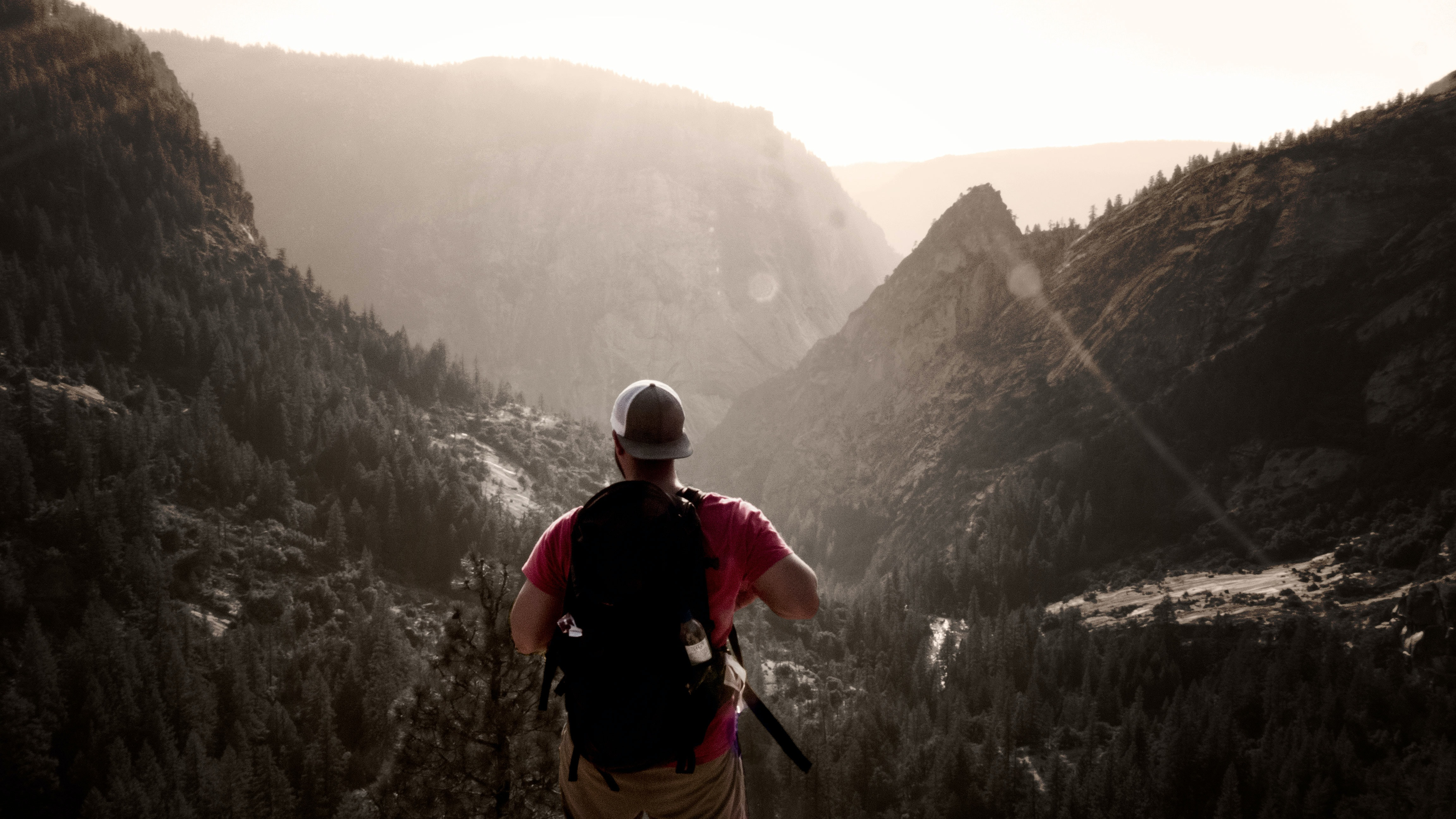 man standing on elevated ground facing mountains during daytime
