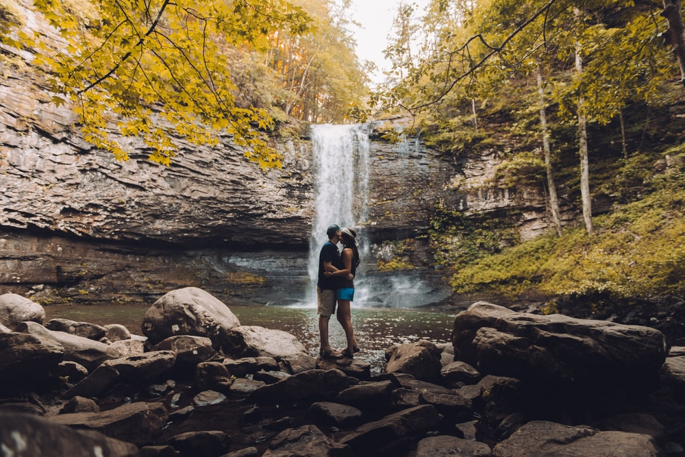 couples kissing in front of waterfalls