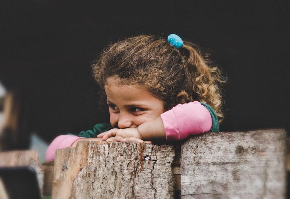 girl leaning on wood log