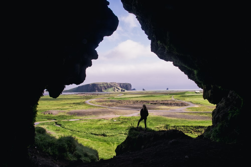 woman standing on rock formation during daytimr