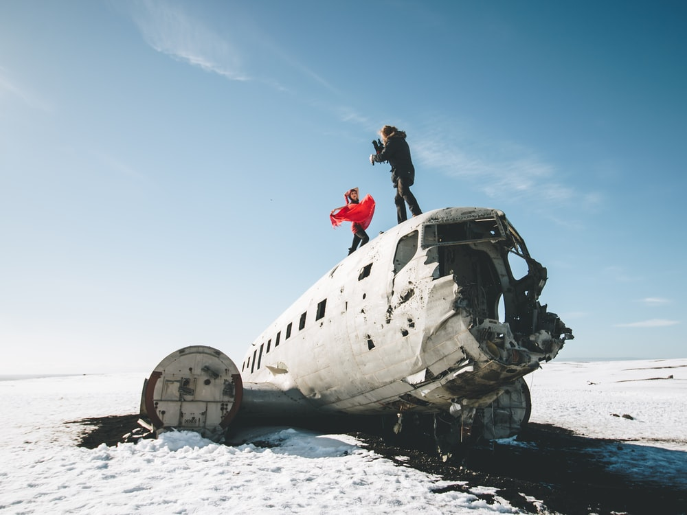 two person standing on top of wrecked airplane at daytime