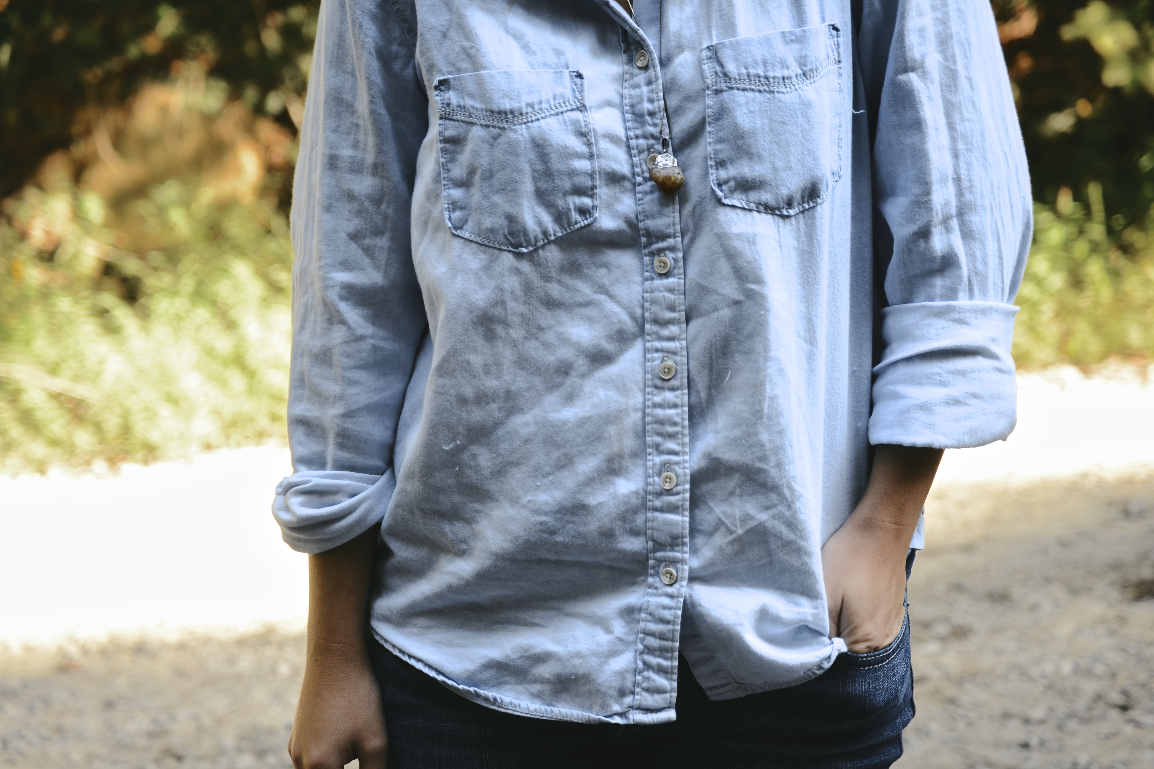 Person's torso wearing a denim chambray shirt with cuffed sleeves