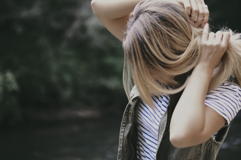 photography of a woman in striped shirt fixing her hair