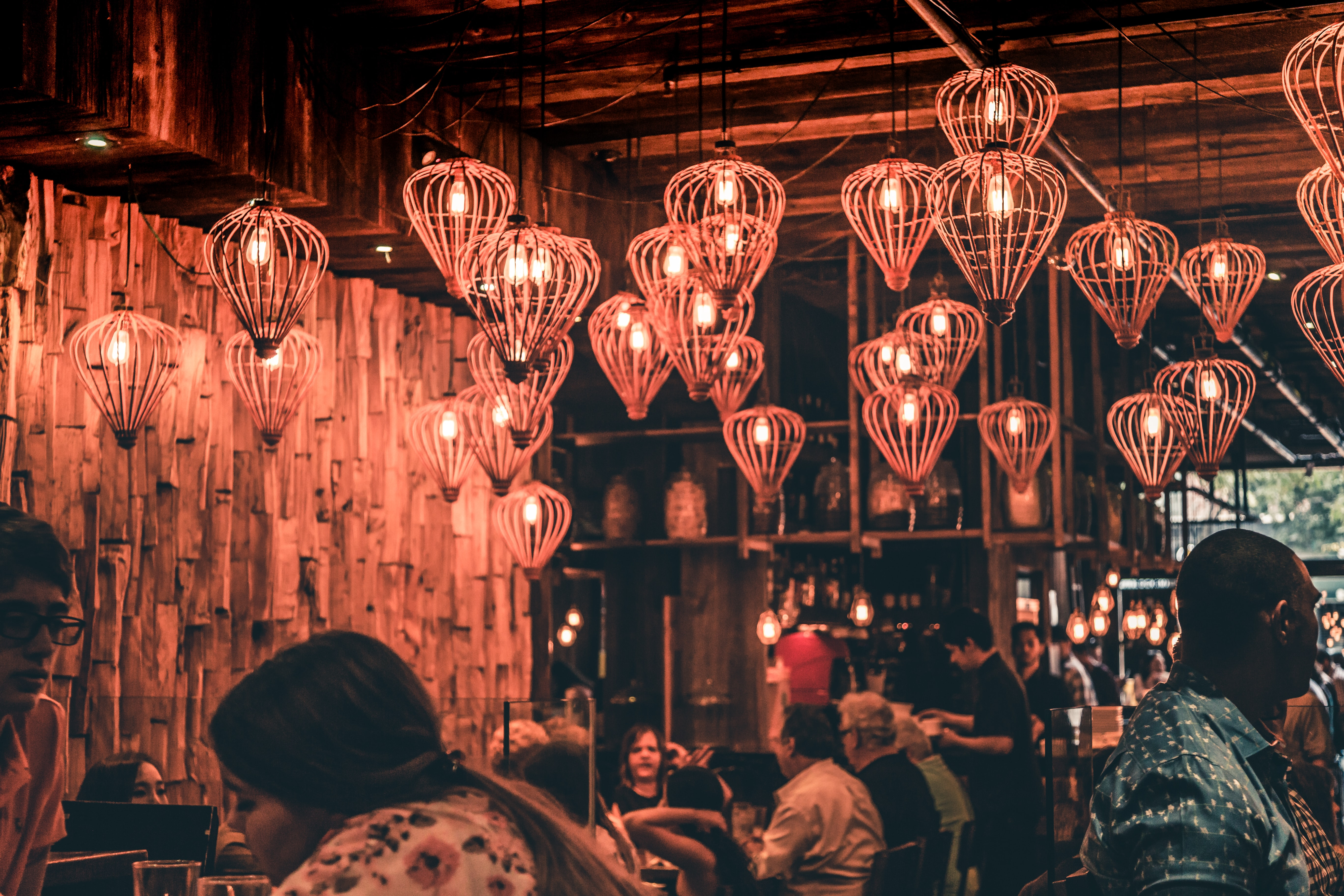 Restaurant interior in urban area with many lights shaped like hot air balloons on the ceiling