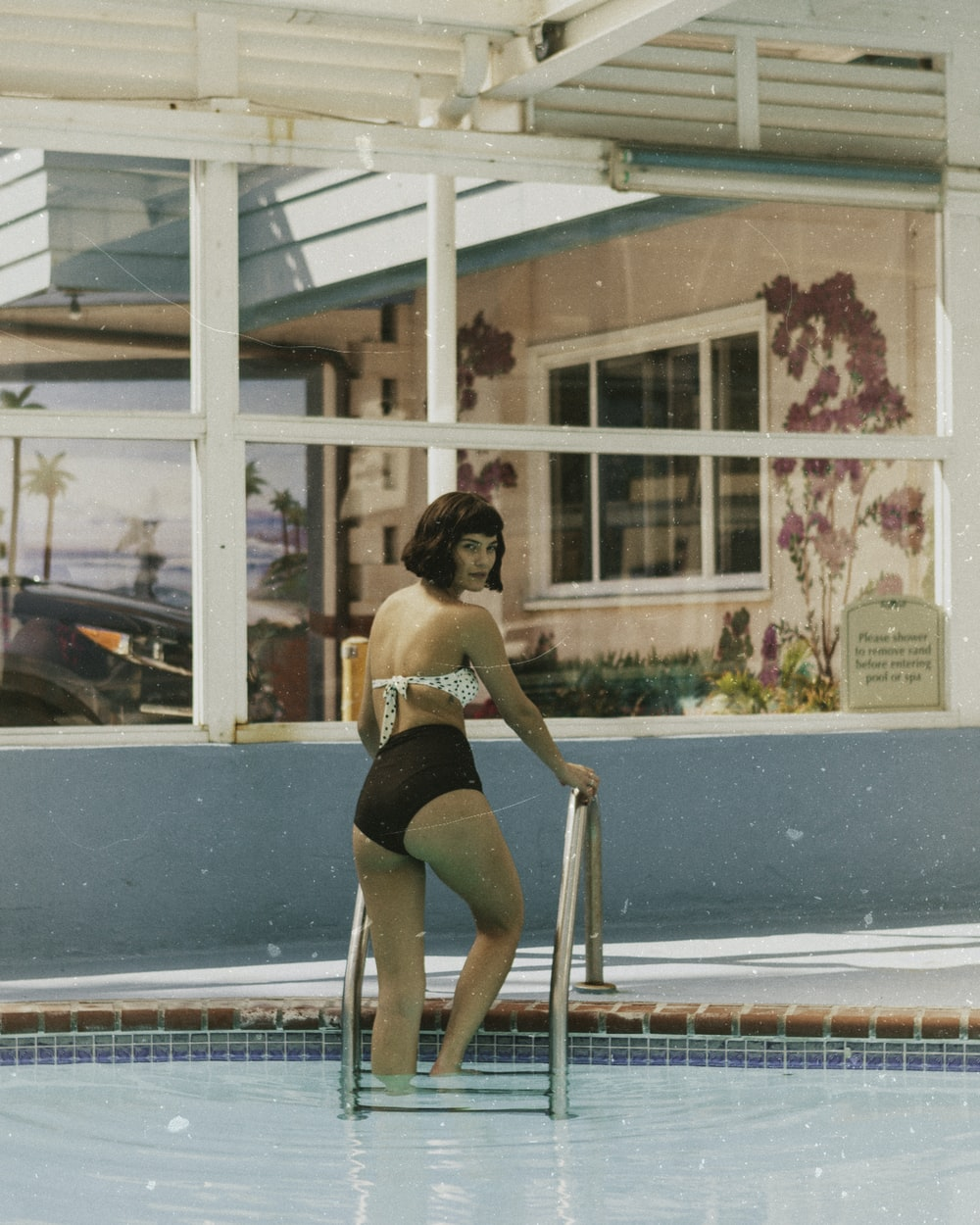 woman standing on pool ladder at daytime