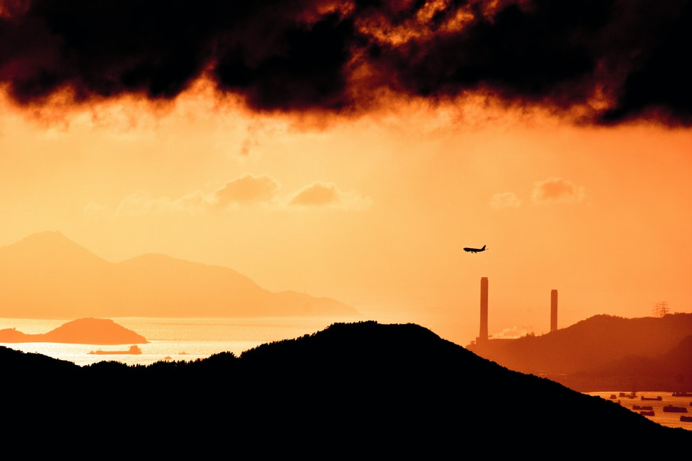 landscape photography of plane in flight over the mountain