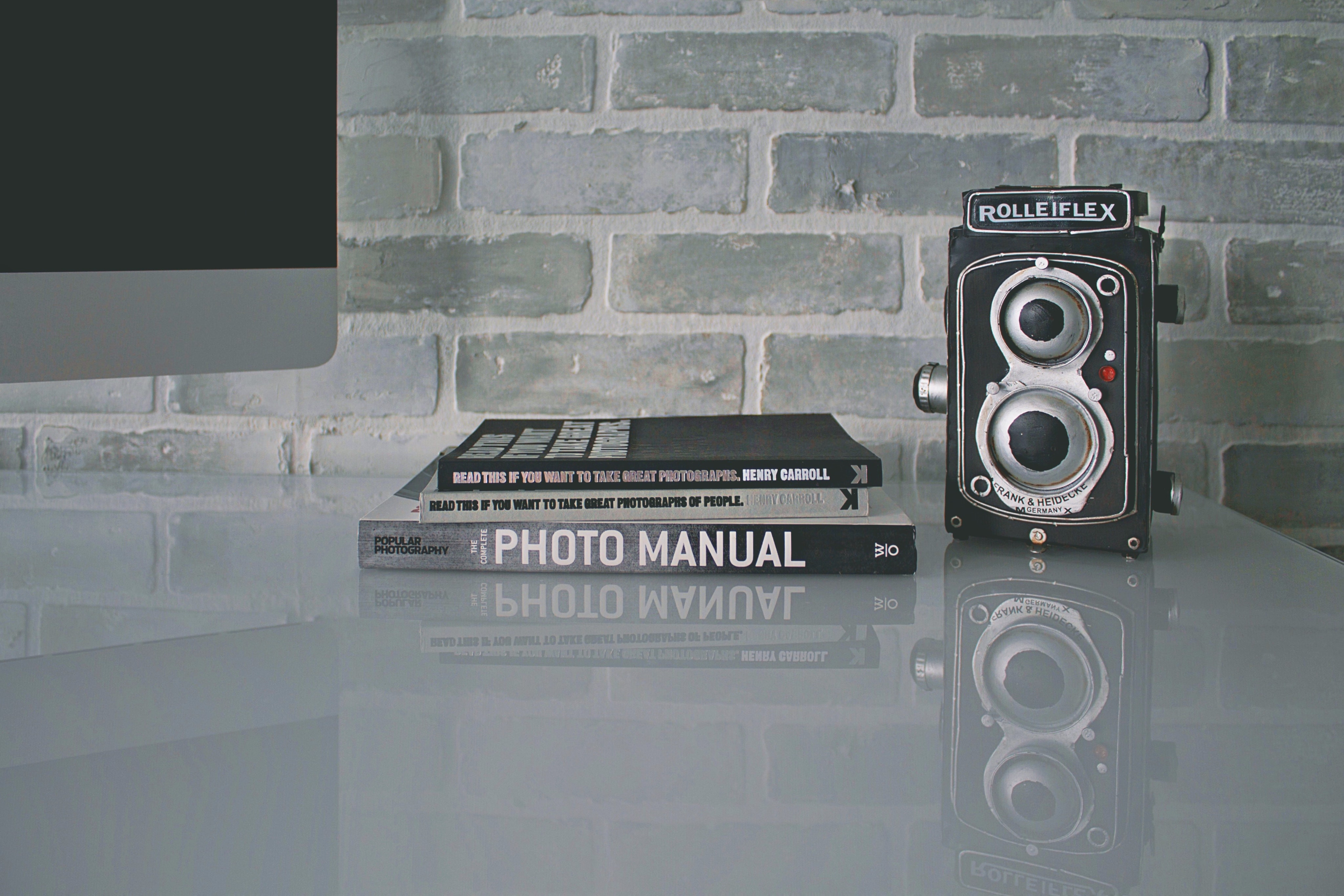 two books beside land camera on table