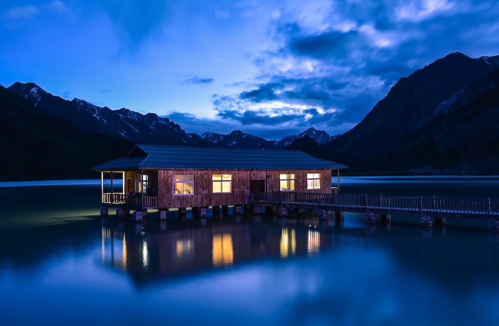 house at the lake with bridge near mountains