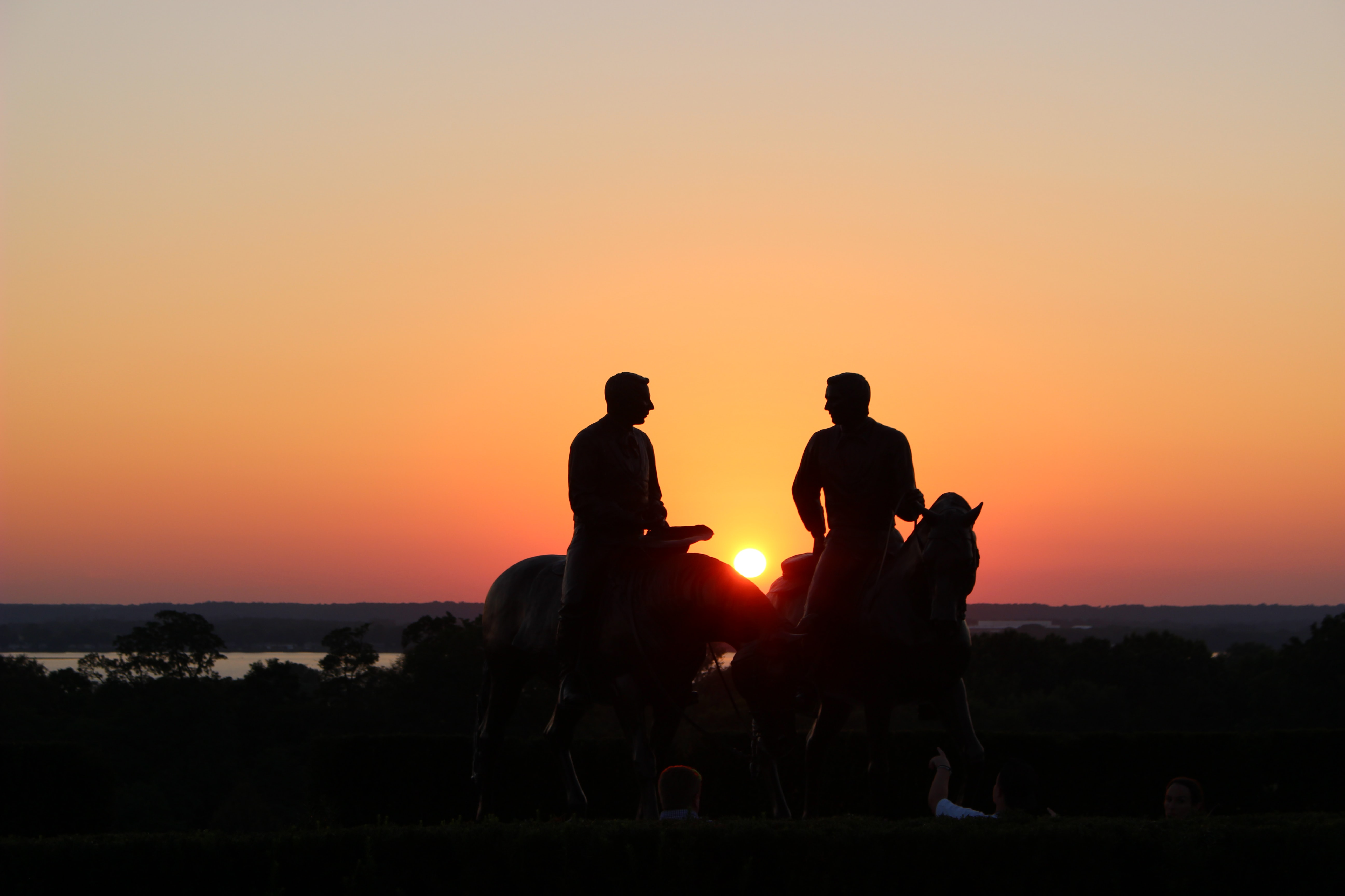 silhouette of two person riding on horse during golden hour