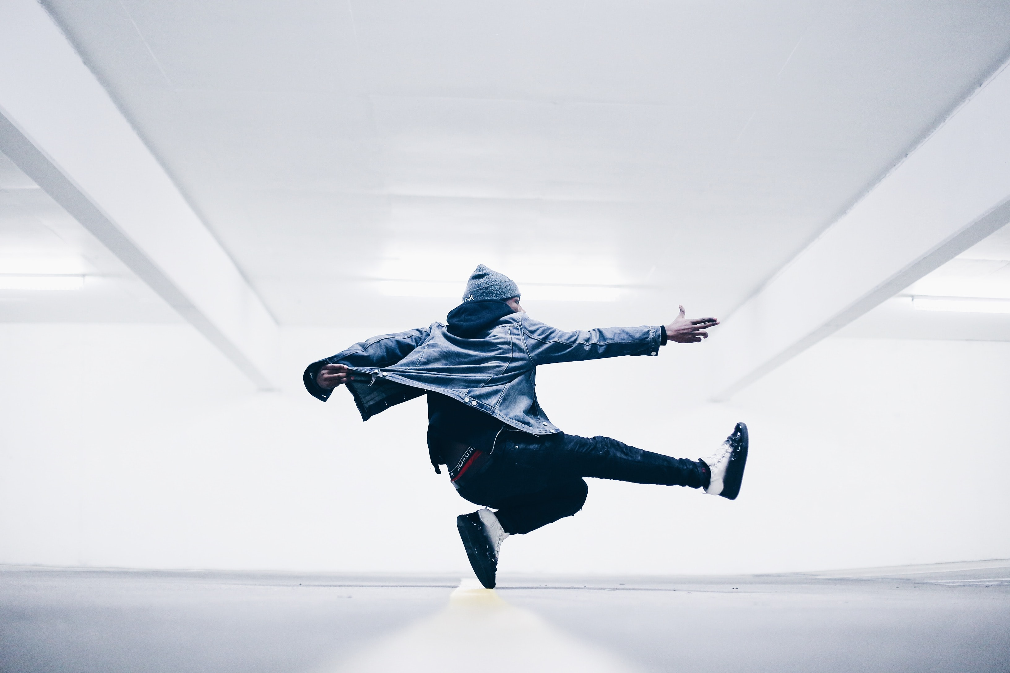 Breakdancer spinning in midair in white dance studio in North Hollywood