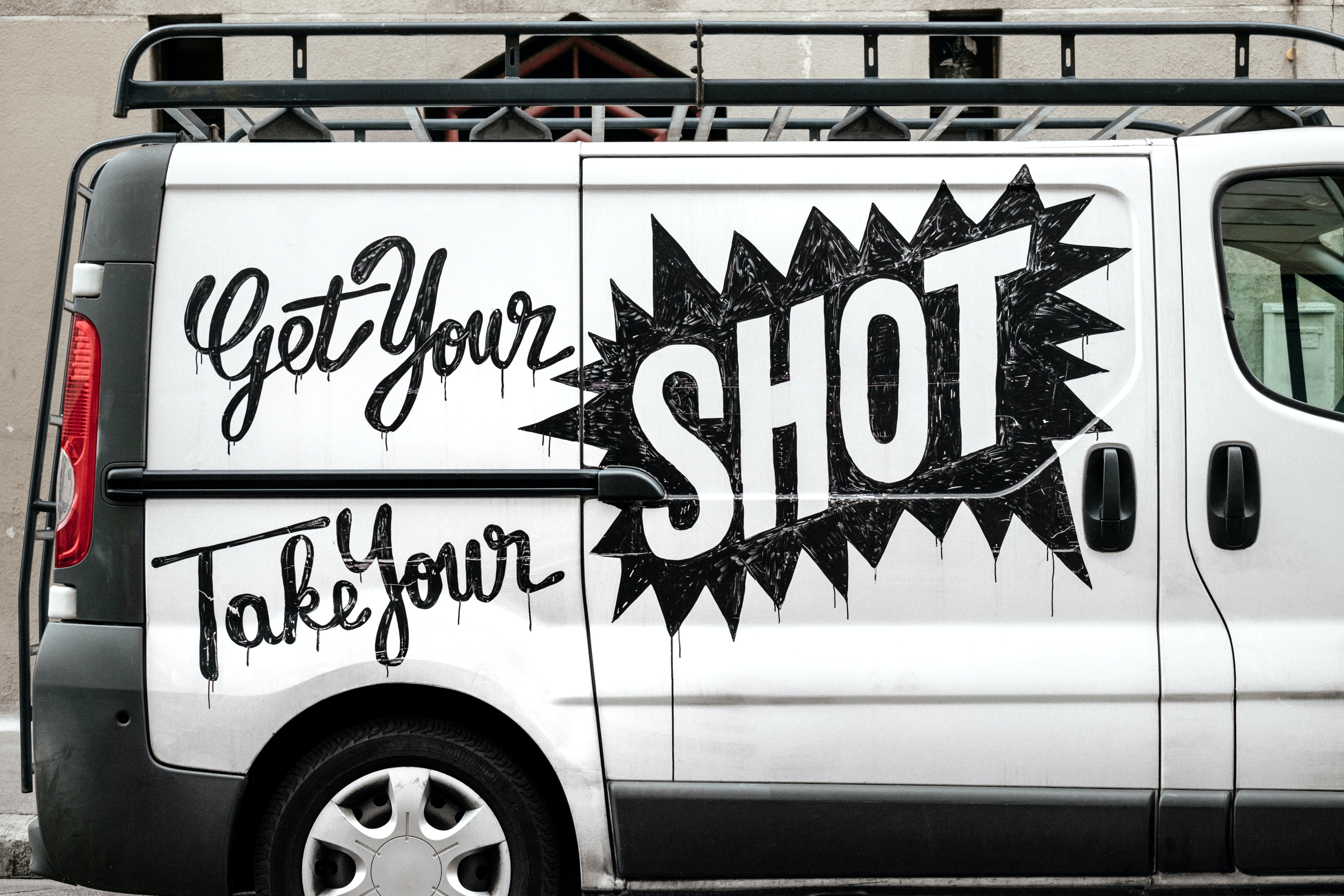 white and black van with Get Your Shot text