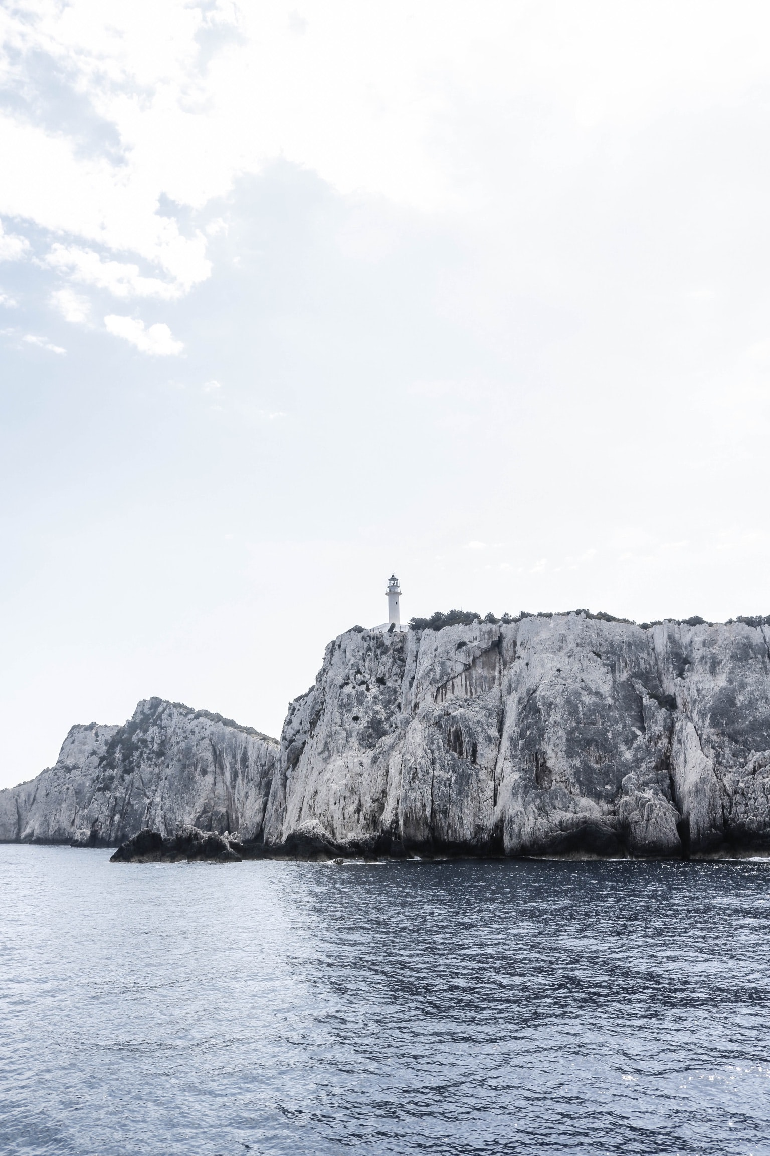 grayscale photography of lighthouse on cliff