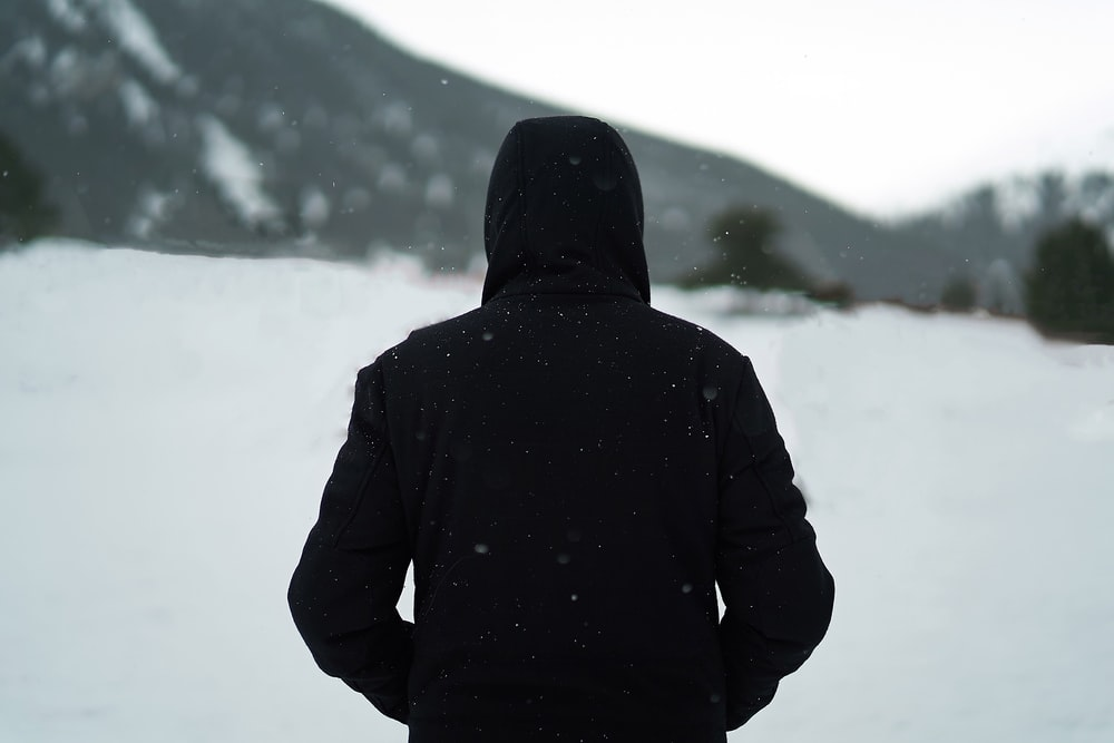person wearing black hoodie standing on snow field during daytime