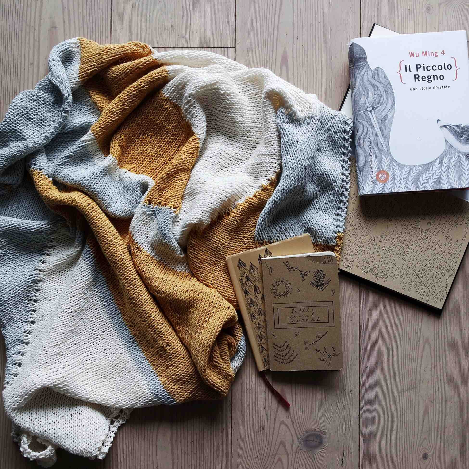 A quilted blanket, notebooks, and a book on a wood floor