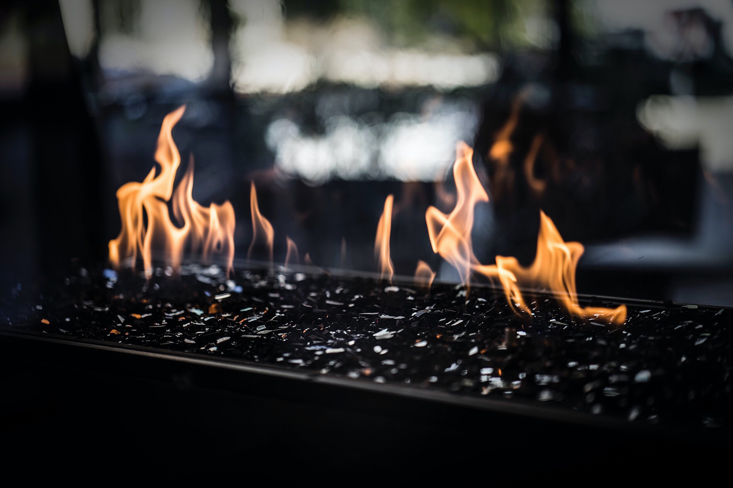 Flames of a charcoal stone fireplace on an outdoor patio