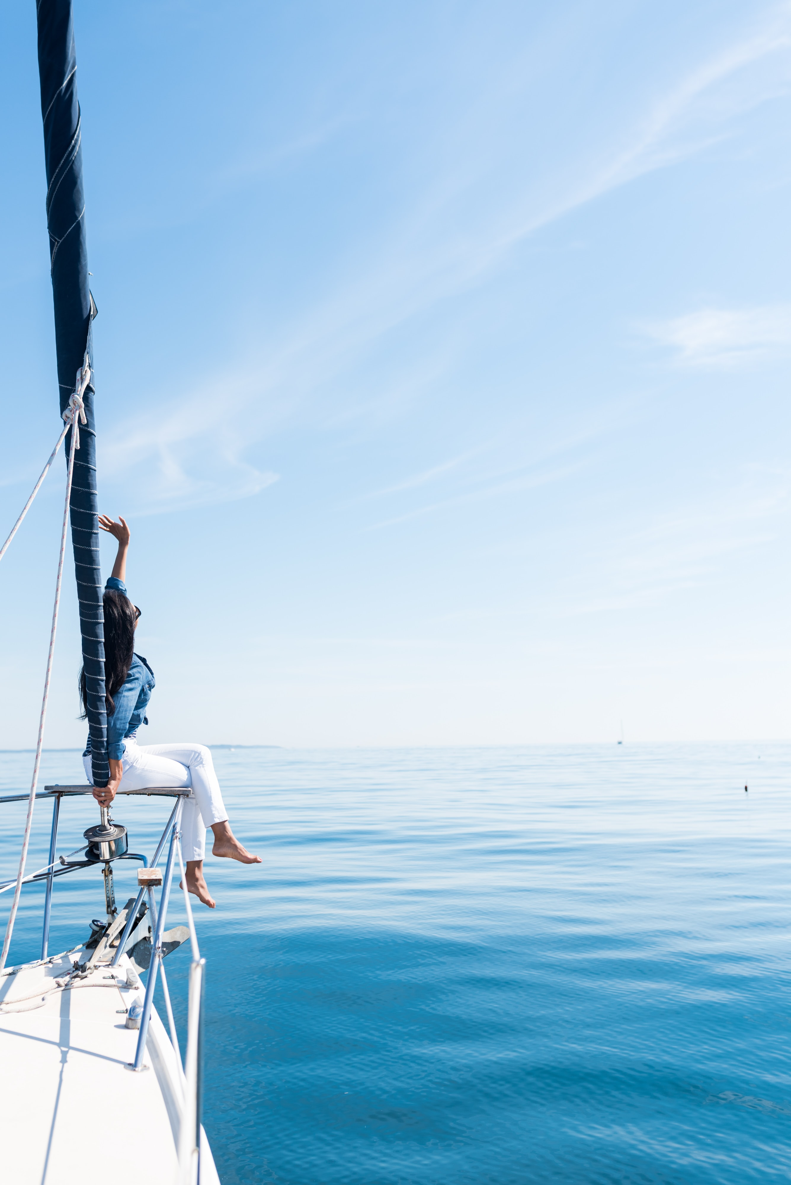 woman on yacht holding a sail at the ocean