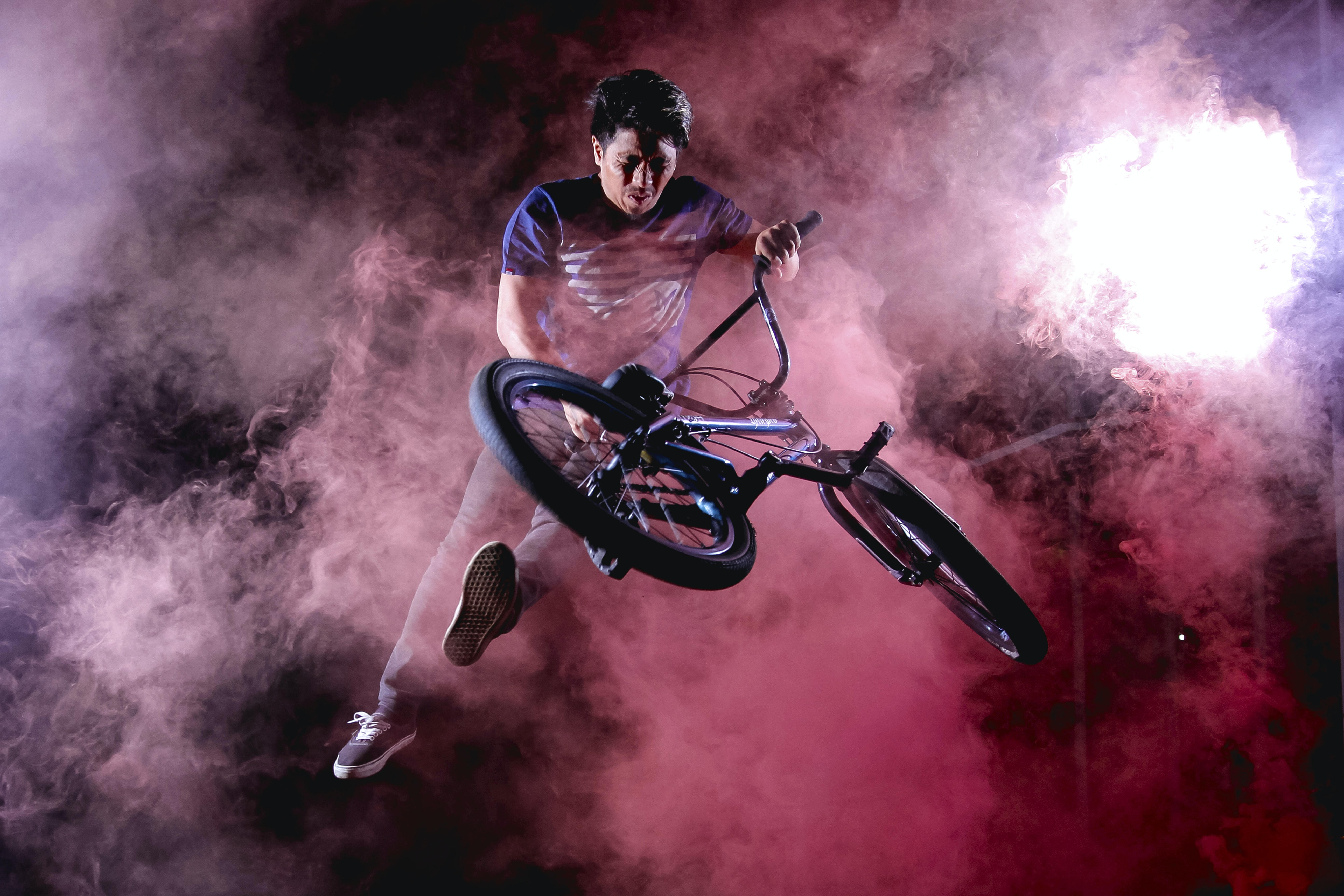 A man does a trick on a bike surrounded by purple and pink fog