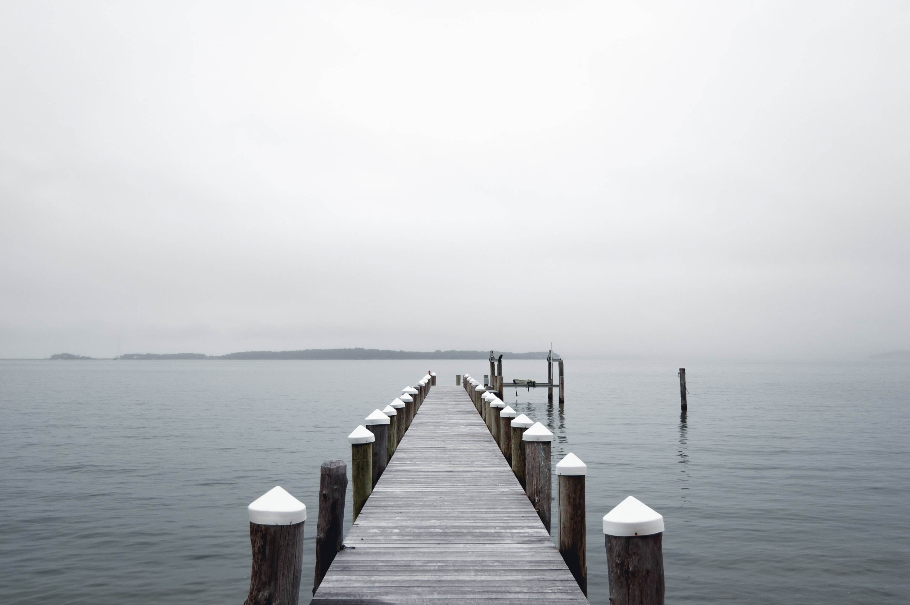 gray wooden dock far from mountain at daytime