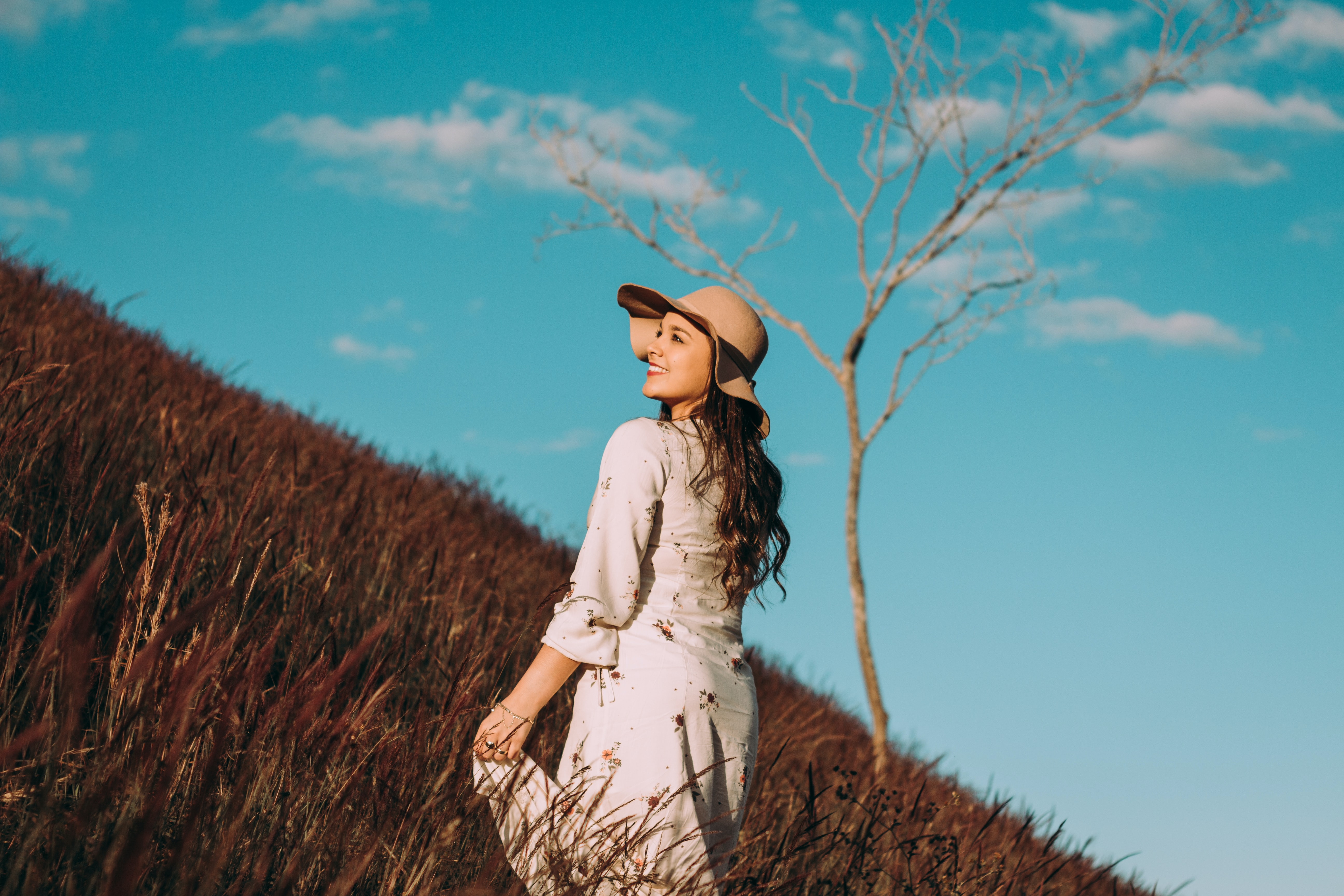 A woman in a hat and white dress smiles in a field against a blue sky