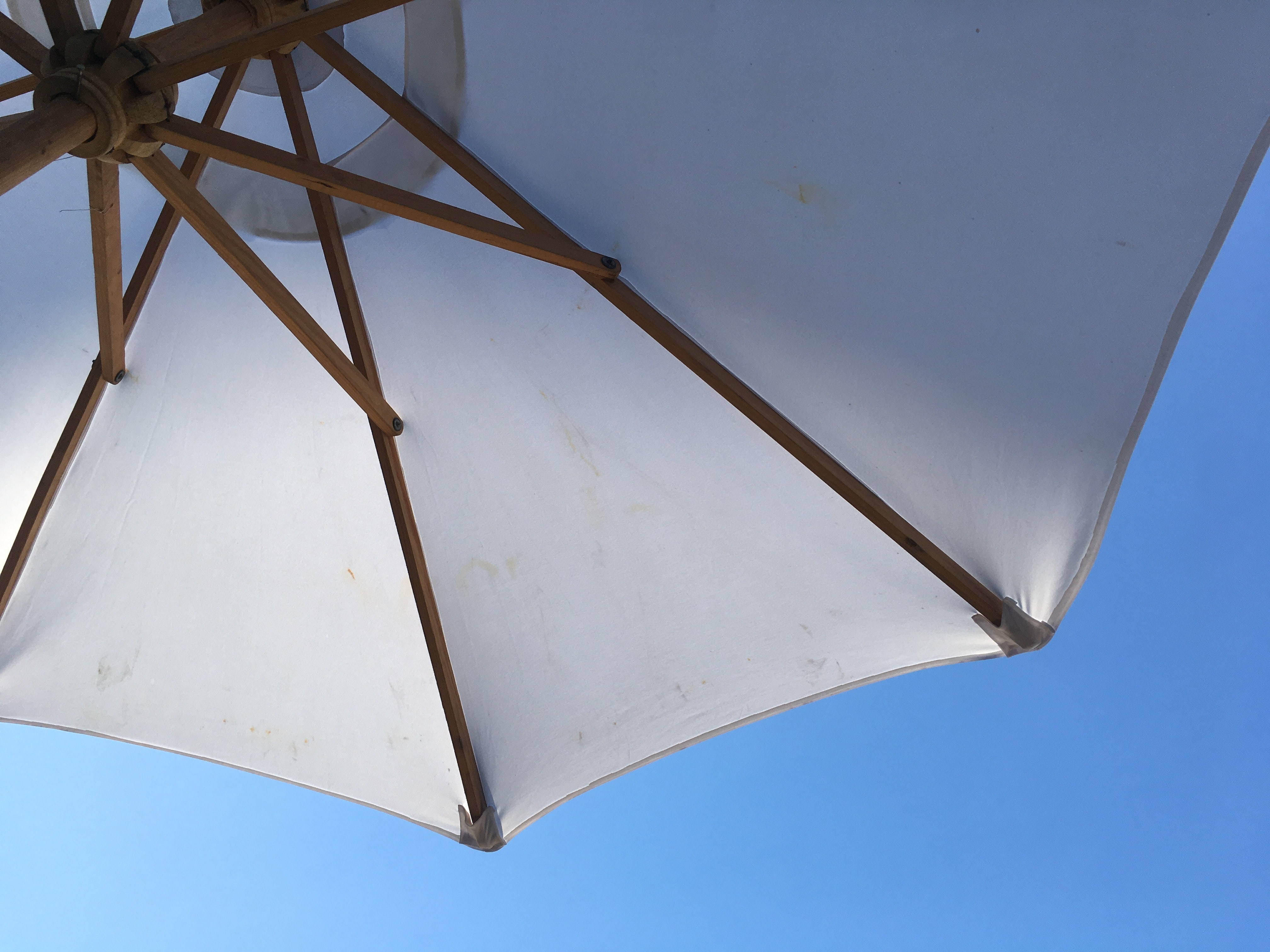 A low-angle shot of a white parasol against a blue sky