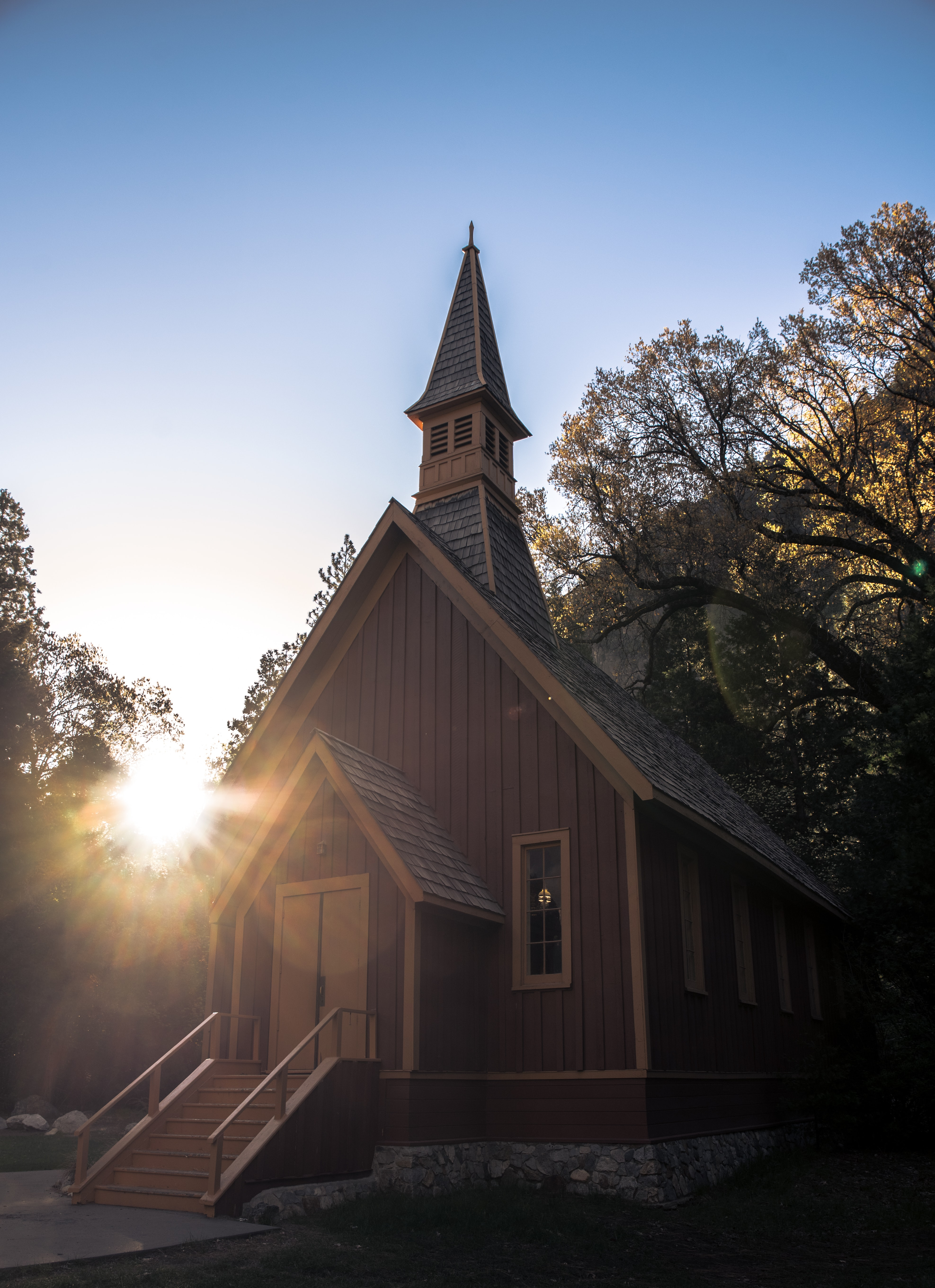 A small church building surrounded by trees, with the sunset in the background.