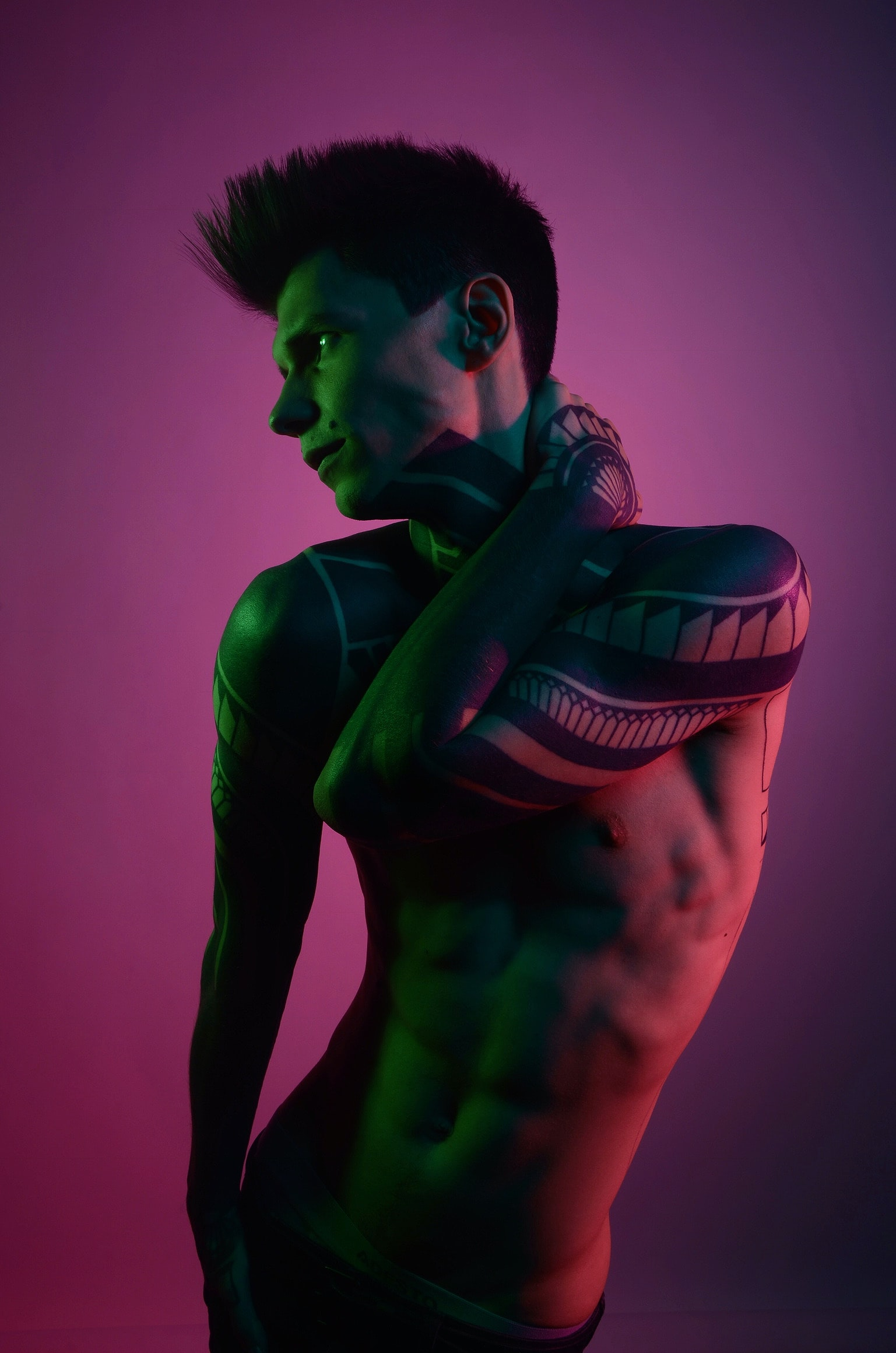 Naked model with tattoo sleeves poses against a pink background