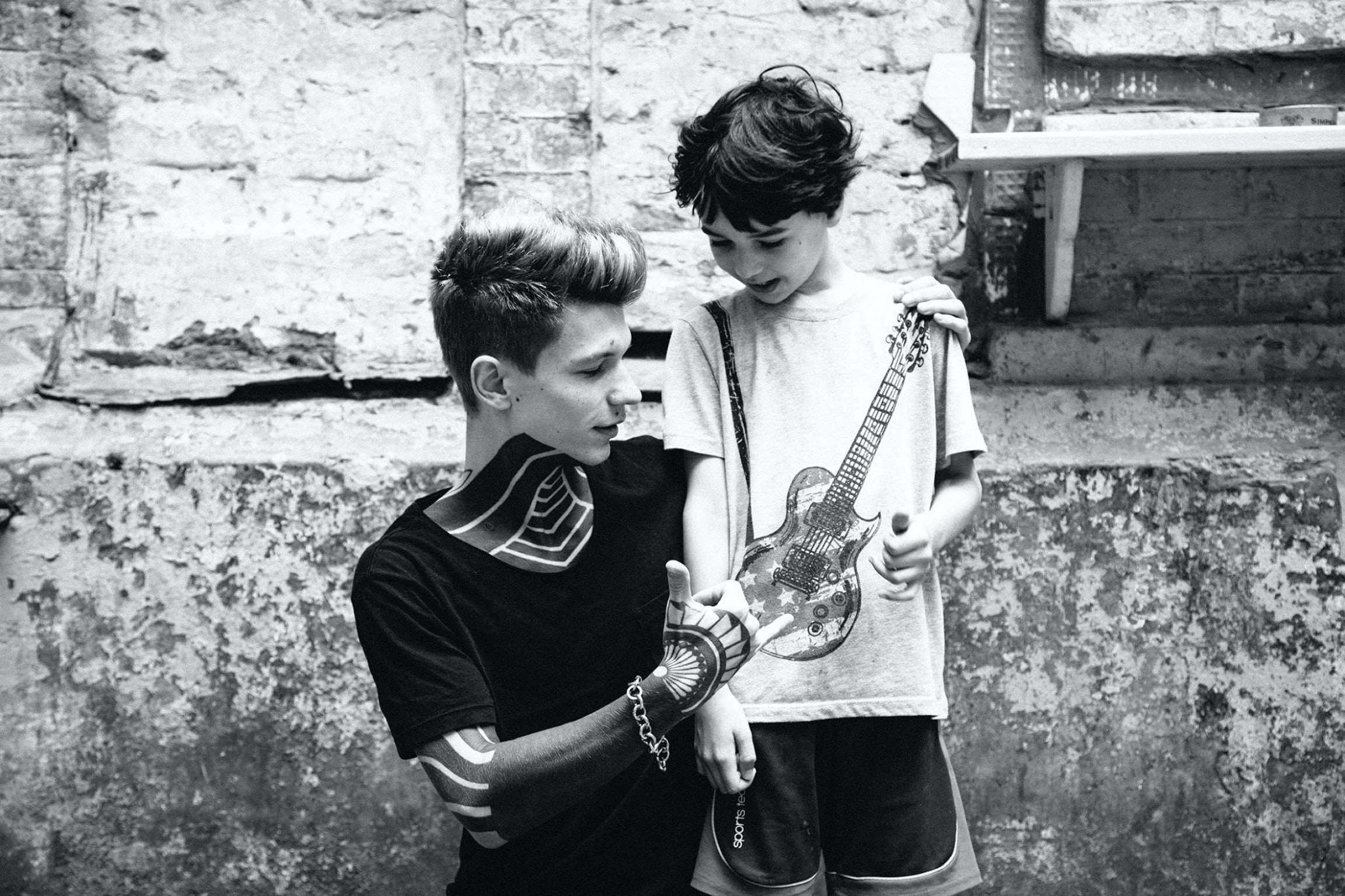 man and boy looking on guitar in grayscale photo