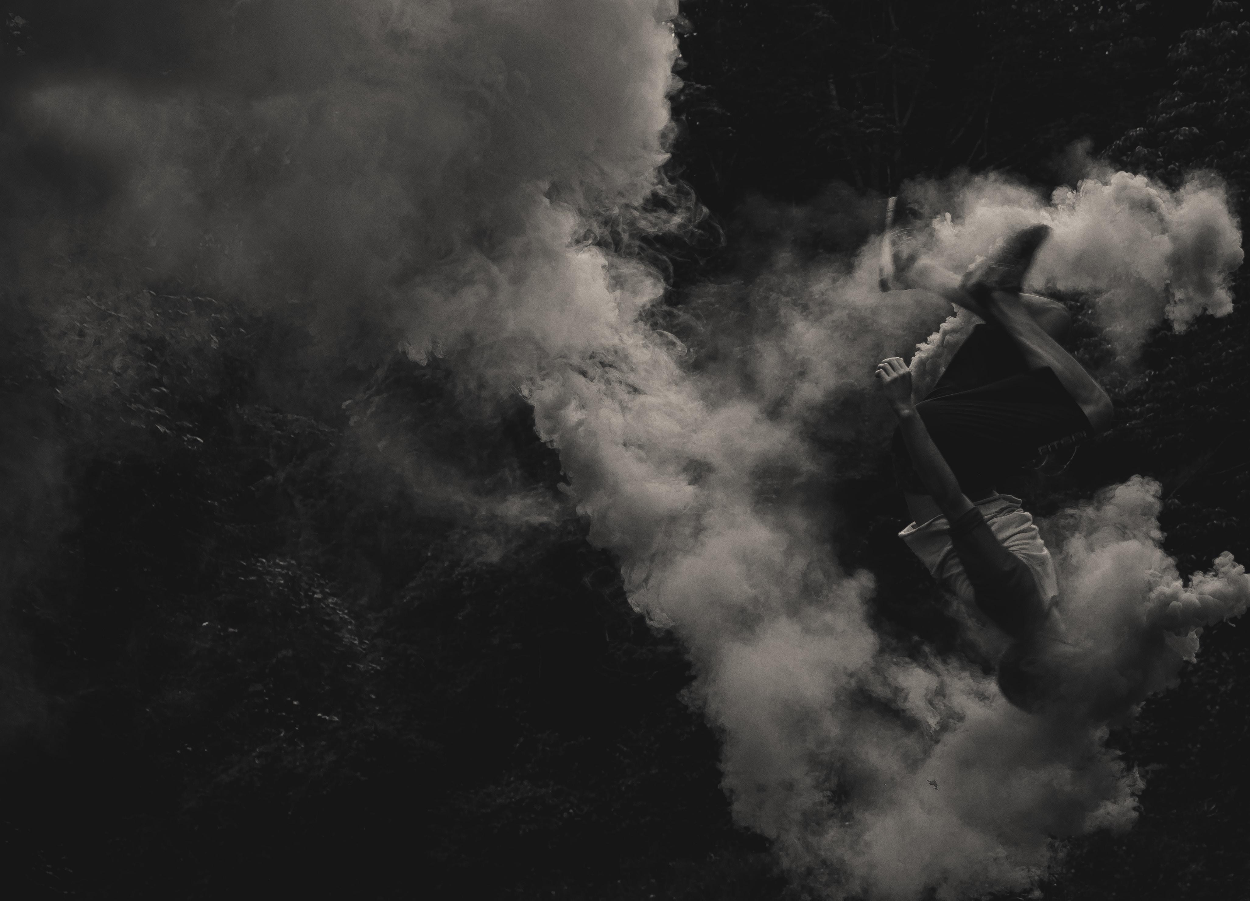 A person doing a backflip through a cloud of smoke.